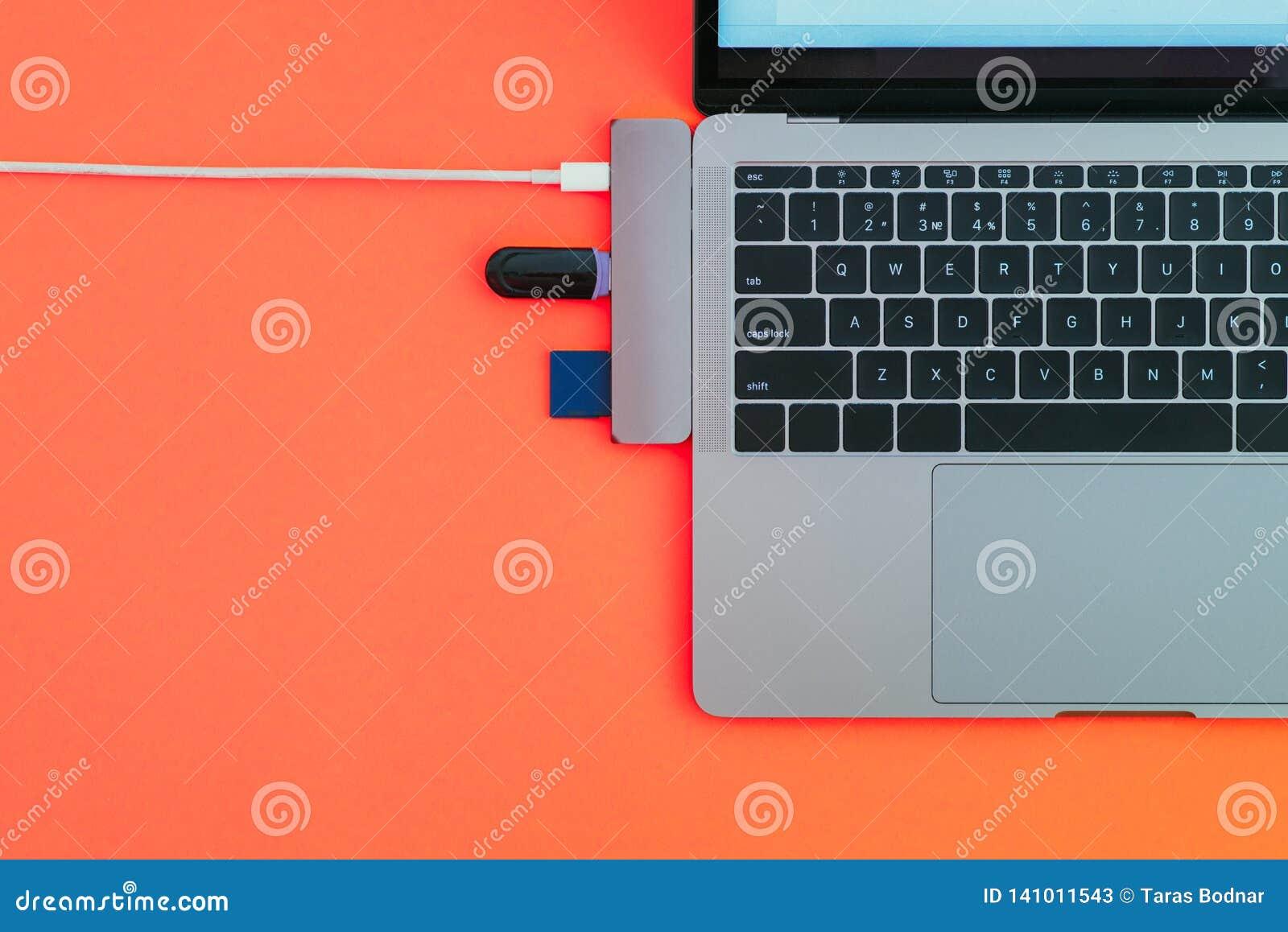 Nowożytny laptop z USB typem adaptator i błysk przejażdżkami odizolowywa na czerwonym tle pojęcia odosobniony technologii biel Co