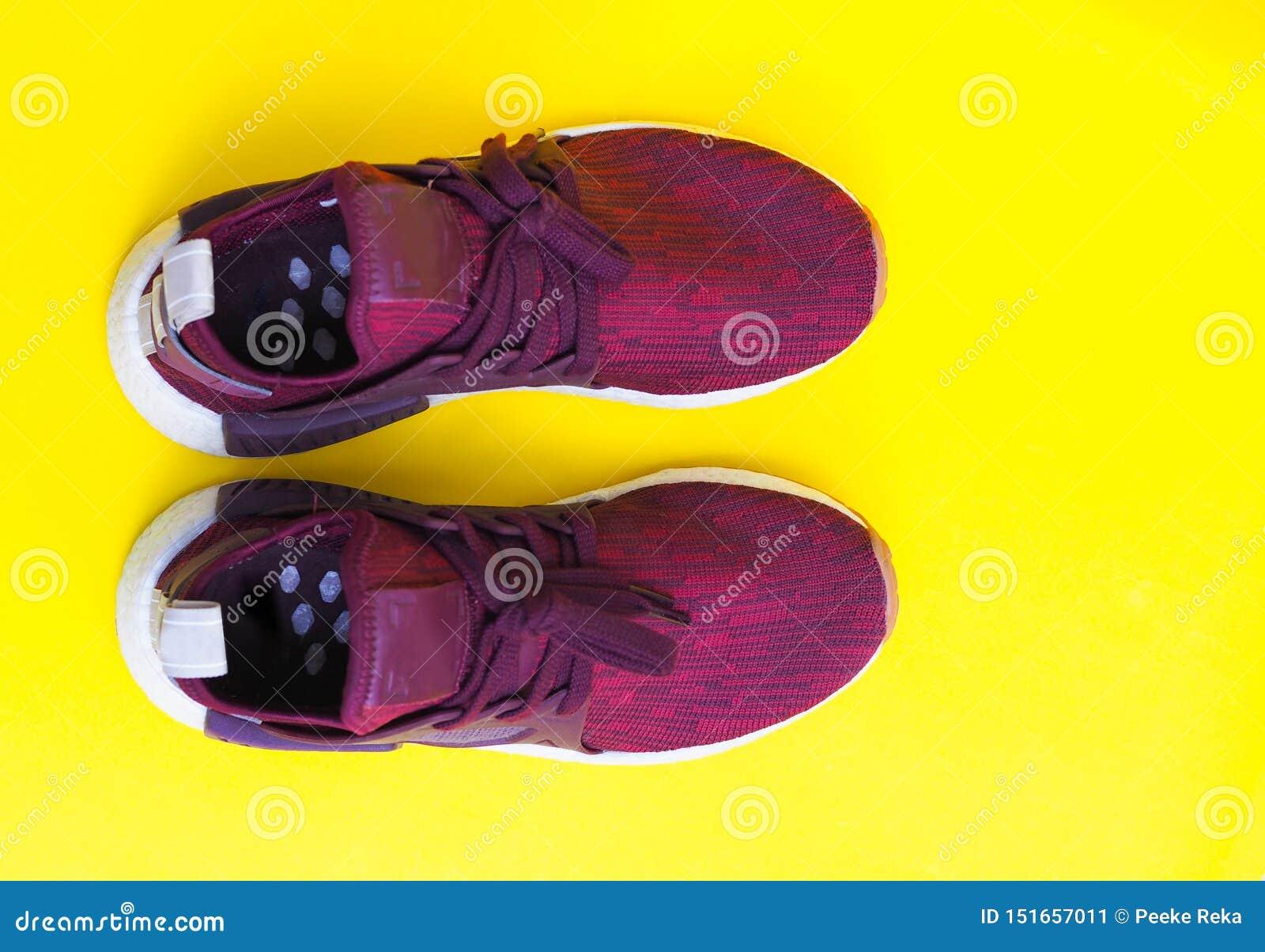 Nowożytni czerwoni pary mody sneakers odizolowywający na żółtym tle