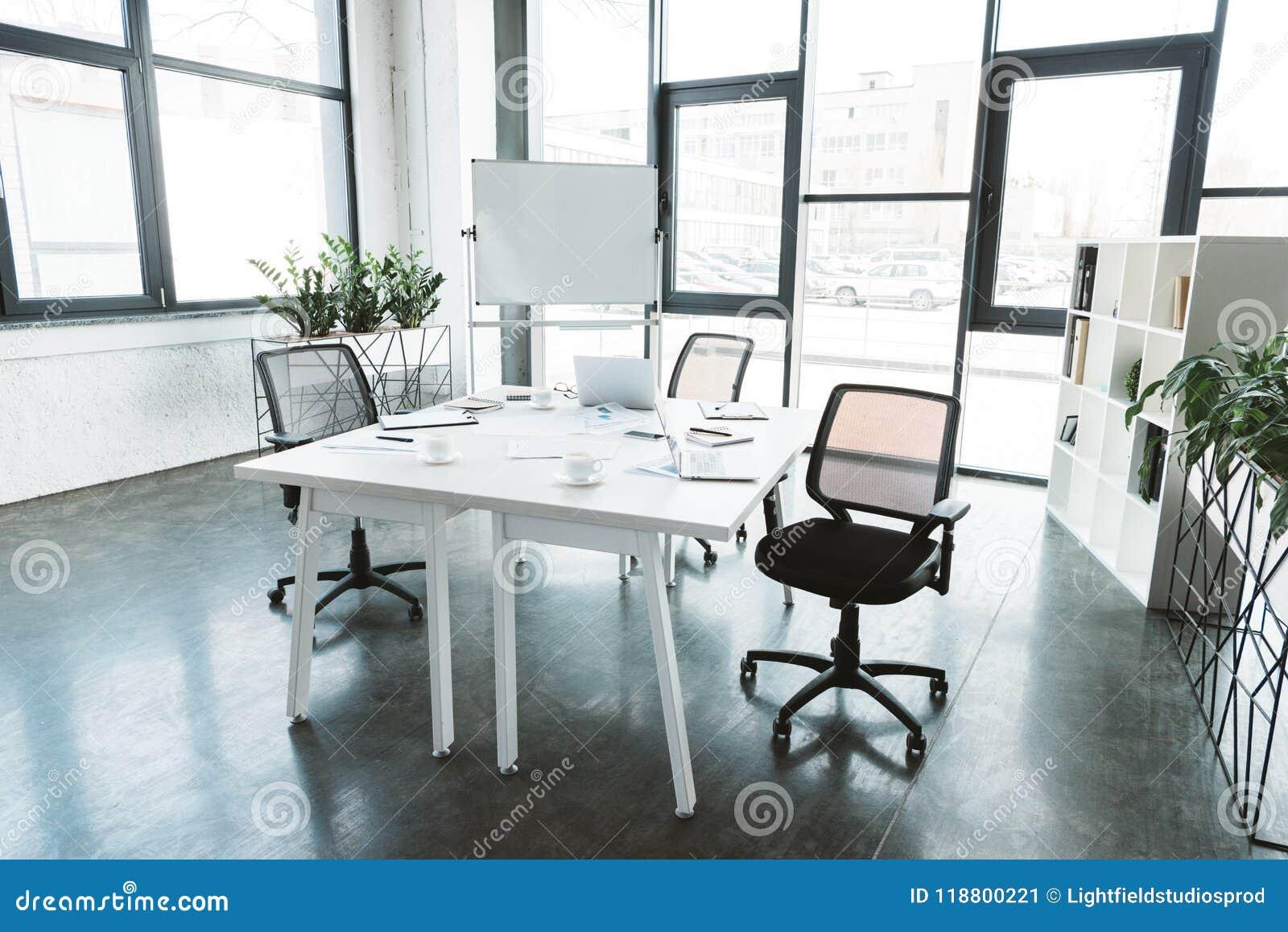 Nowożytny biurowy wnętrze z biurkiem, papiery, krzesła