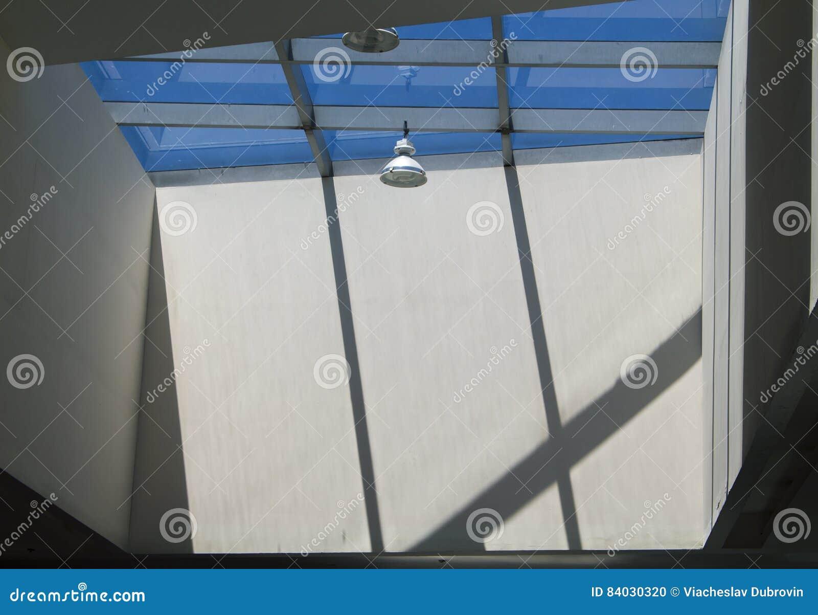 Nowożytny budynku oświetlenie z round lampowymi i dachowymi okno Betonowe ściany z słońce cieniami i światłem