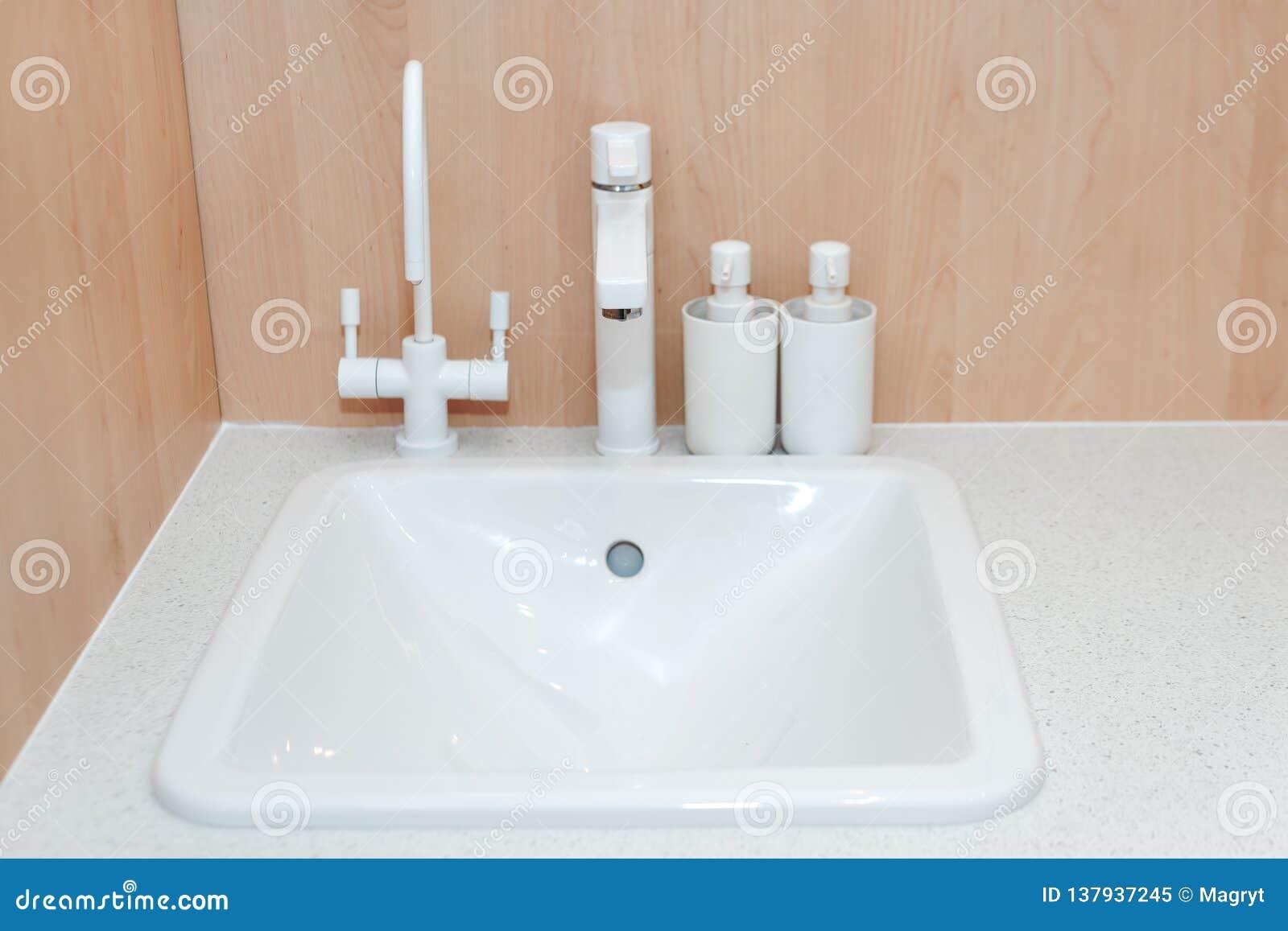 Nowożytny kuchenny biały faucet i ceramiczny kuchenny zlew Minimalistyczni łazienki wnętrza szczegóły