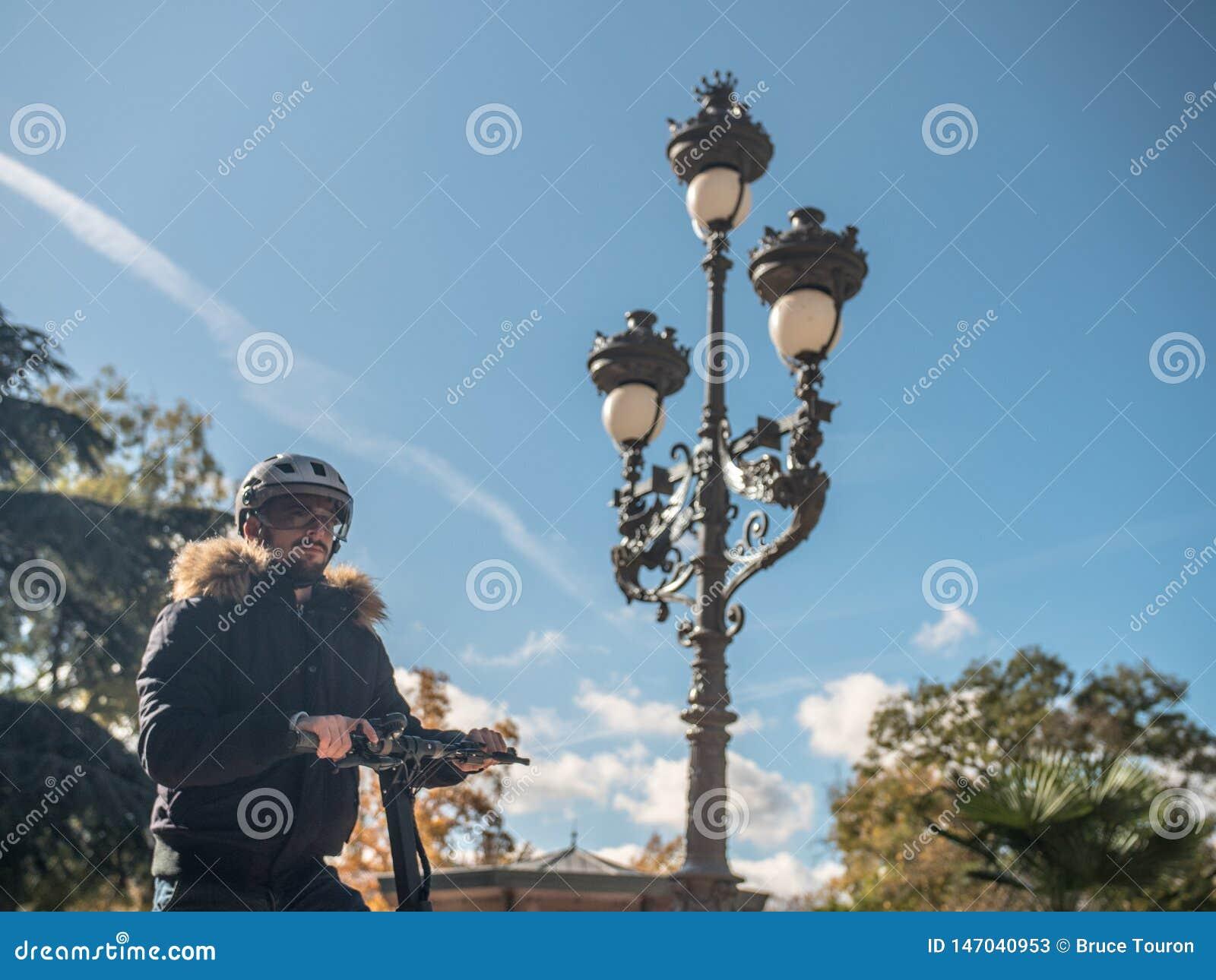 Nowożytny mężczyzna z hełmem Używać Elektryczną hulajnogę w pogodnym parku 7