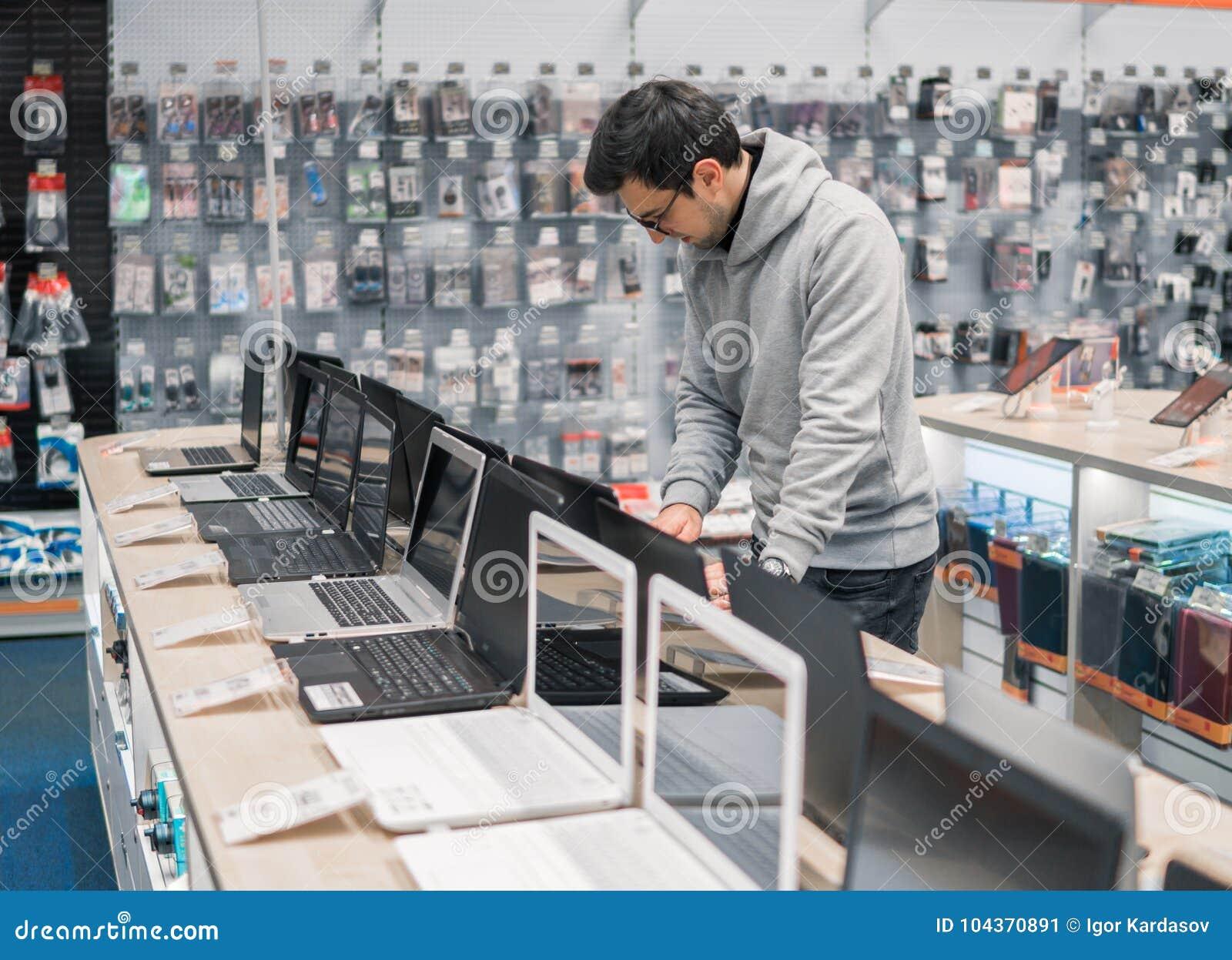 Nowożytny męski klient wybiera laptop w komputerowym sklepie