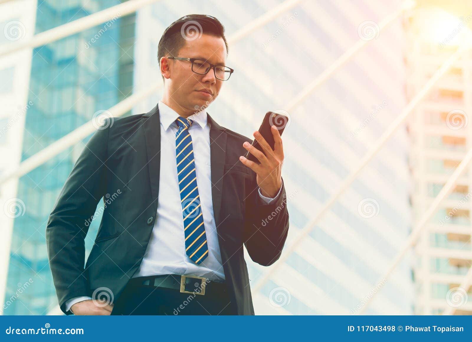Nowożytny młody biznesmen odzieży czerni kostiumu ręki mienia smartphone Fachowa biznesowego mężczyzna pozycja na zewnątrz biura