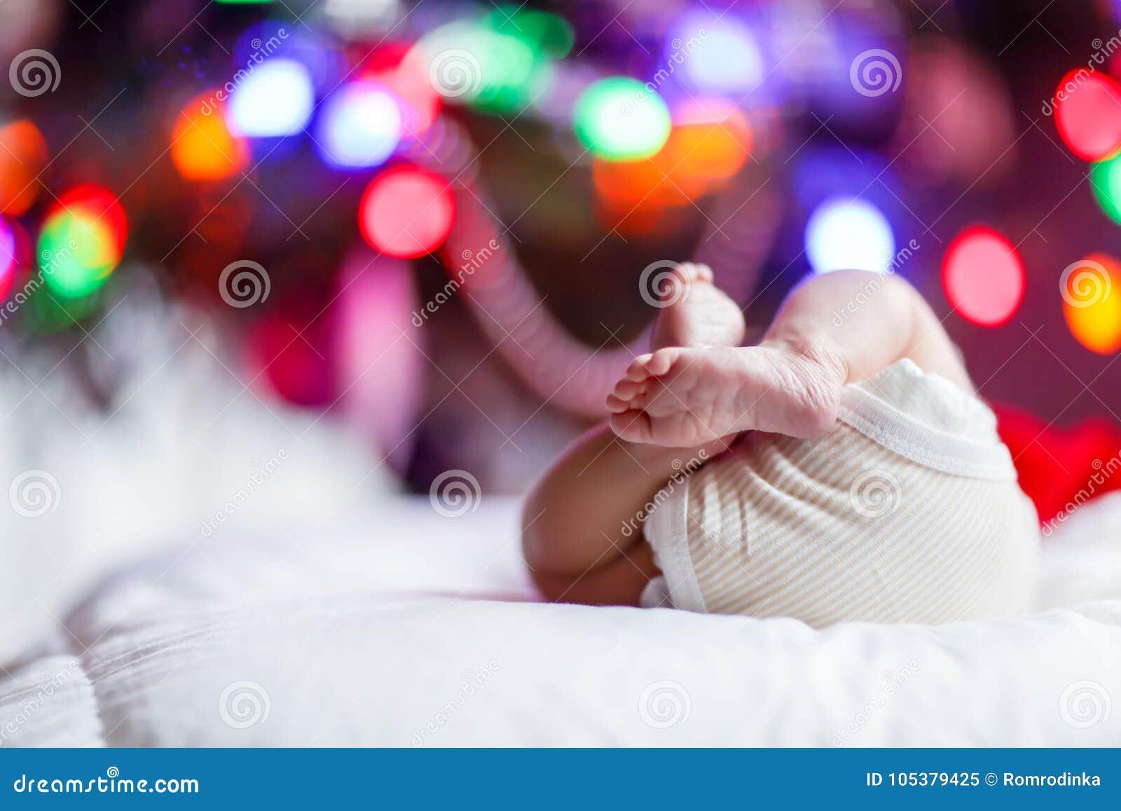 Nowonarodzeni dziecko cieki, pieluszka z choinką i kolorowymi girland światłami i