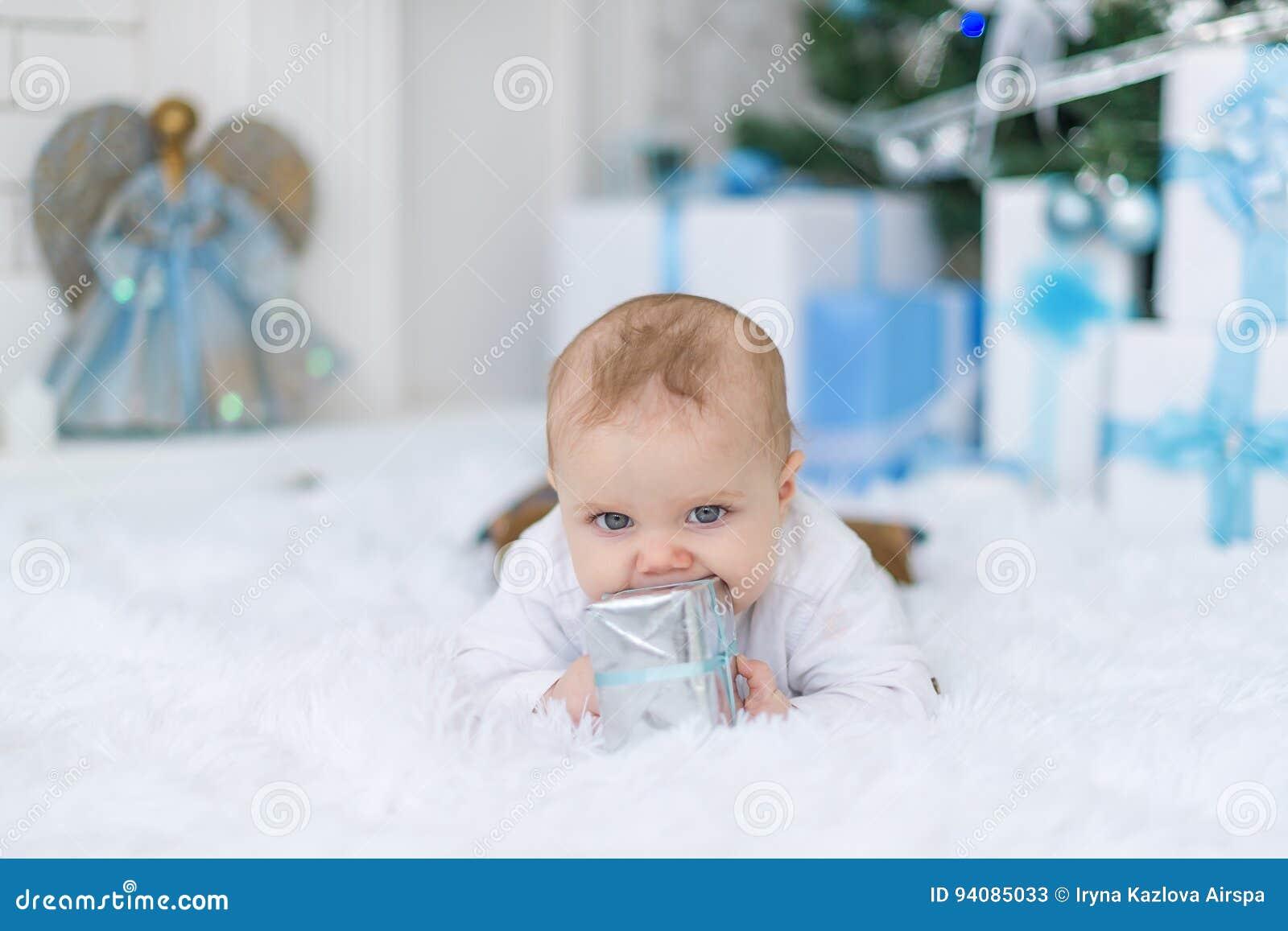 Nowonarodzona chłopiec patrzeje kamerę z prezenta pudełkiem