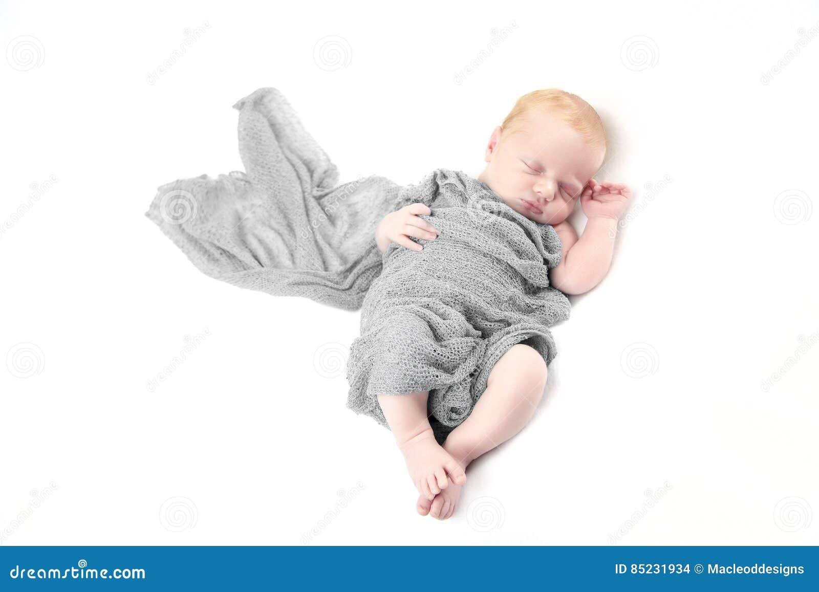 Nowonarodzona chłopiec w szarość opakunku przeciw bielowi