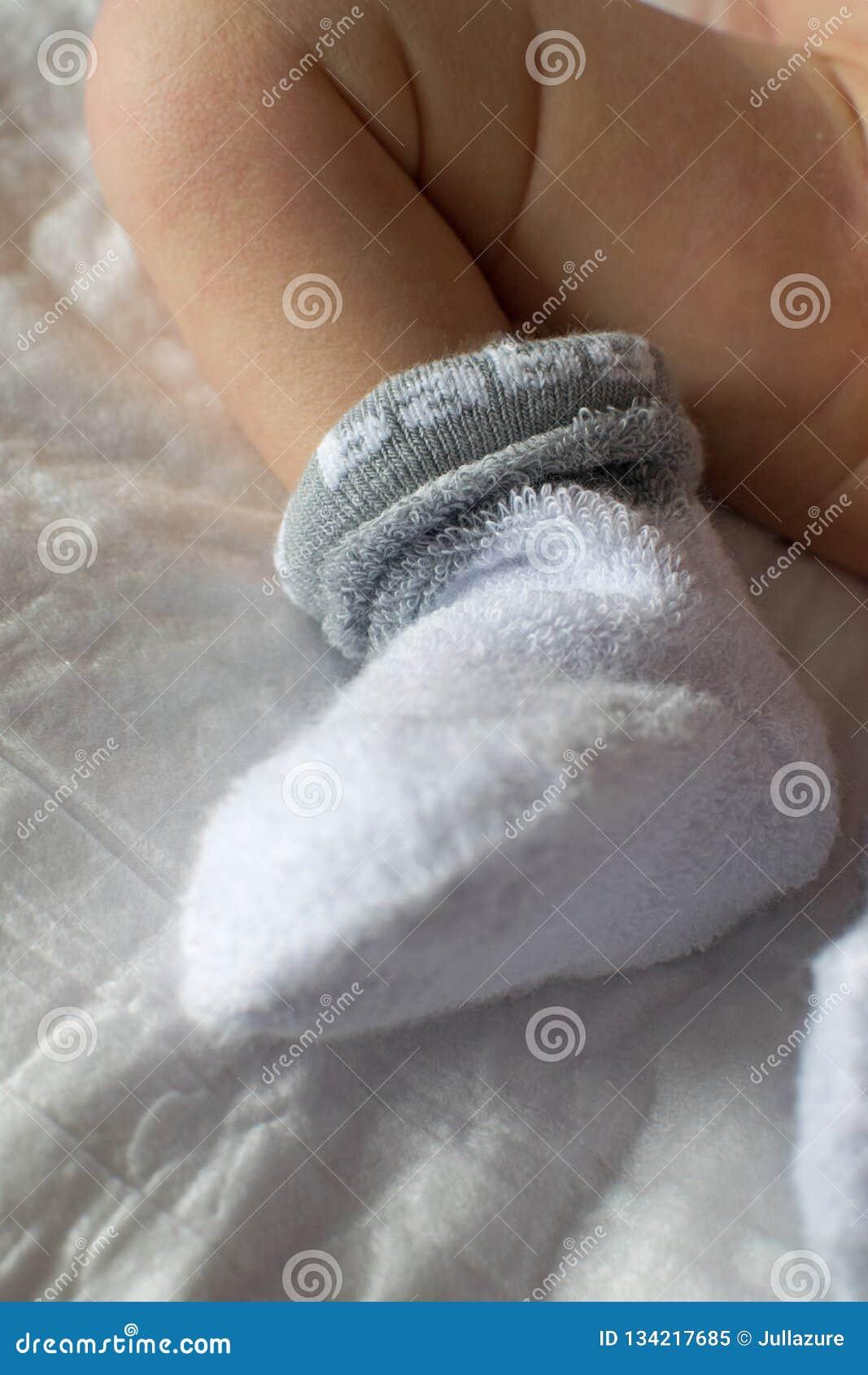 Nowonarodzonych dziecko cieków zamknięty up Dziecko cieki w białych Terry skarpetach, dziecka lying on the beach na łóżku, dzieck
