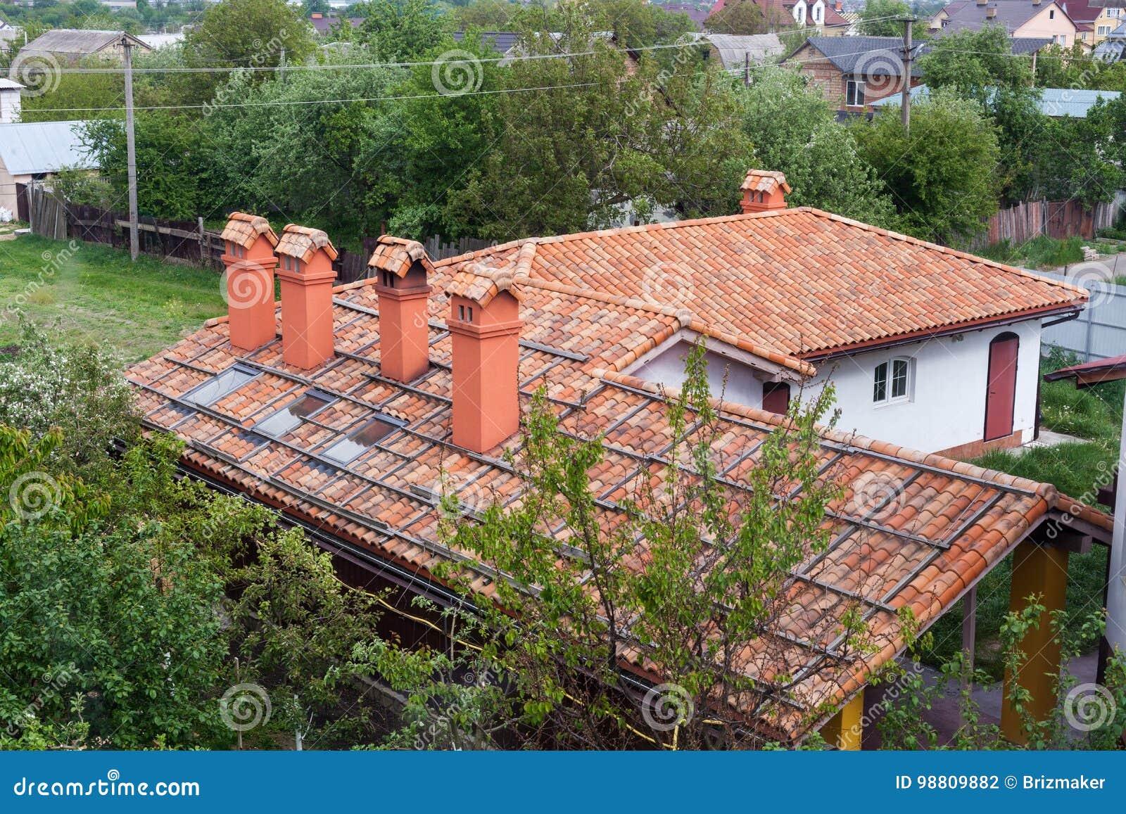 Nowy cegła dom z czerwonym dachowej płytki kominem, plastikowymi okno i podeszczową rynną deseniowym i modularnym,