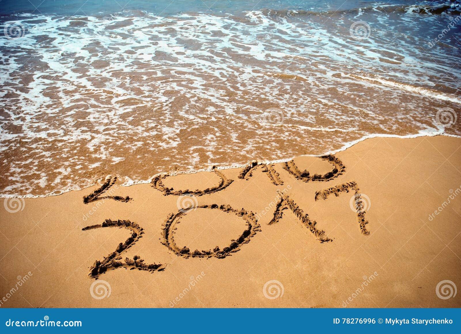 Nowy Rok 2017 jest nadchodzącym pojęciem - inskrypcja 2017, 2016 na plażowym piasku i fala zakrywa cyfry 2016 Nowy Rok 2017 sława