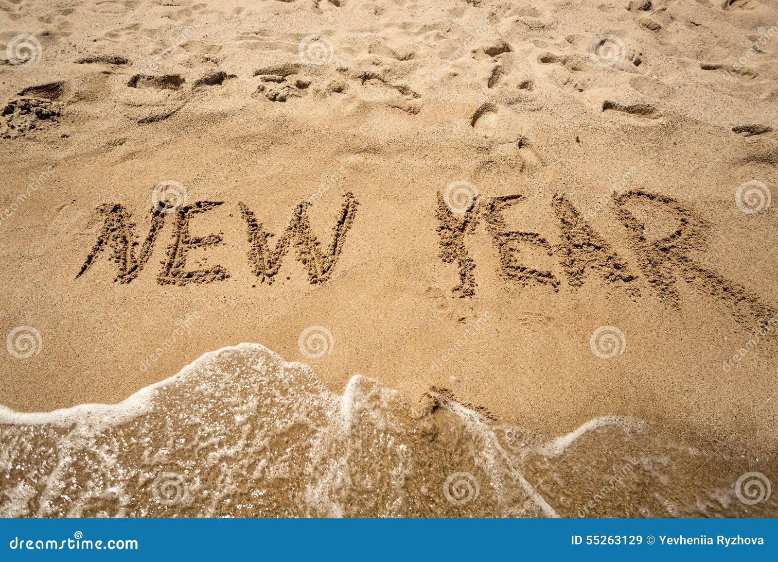 Nowy Rok pisać na piasku i myje fala