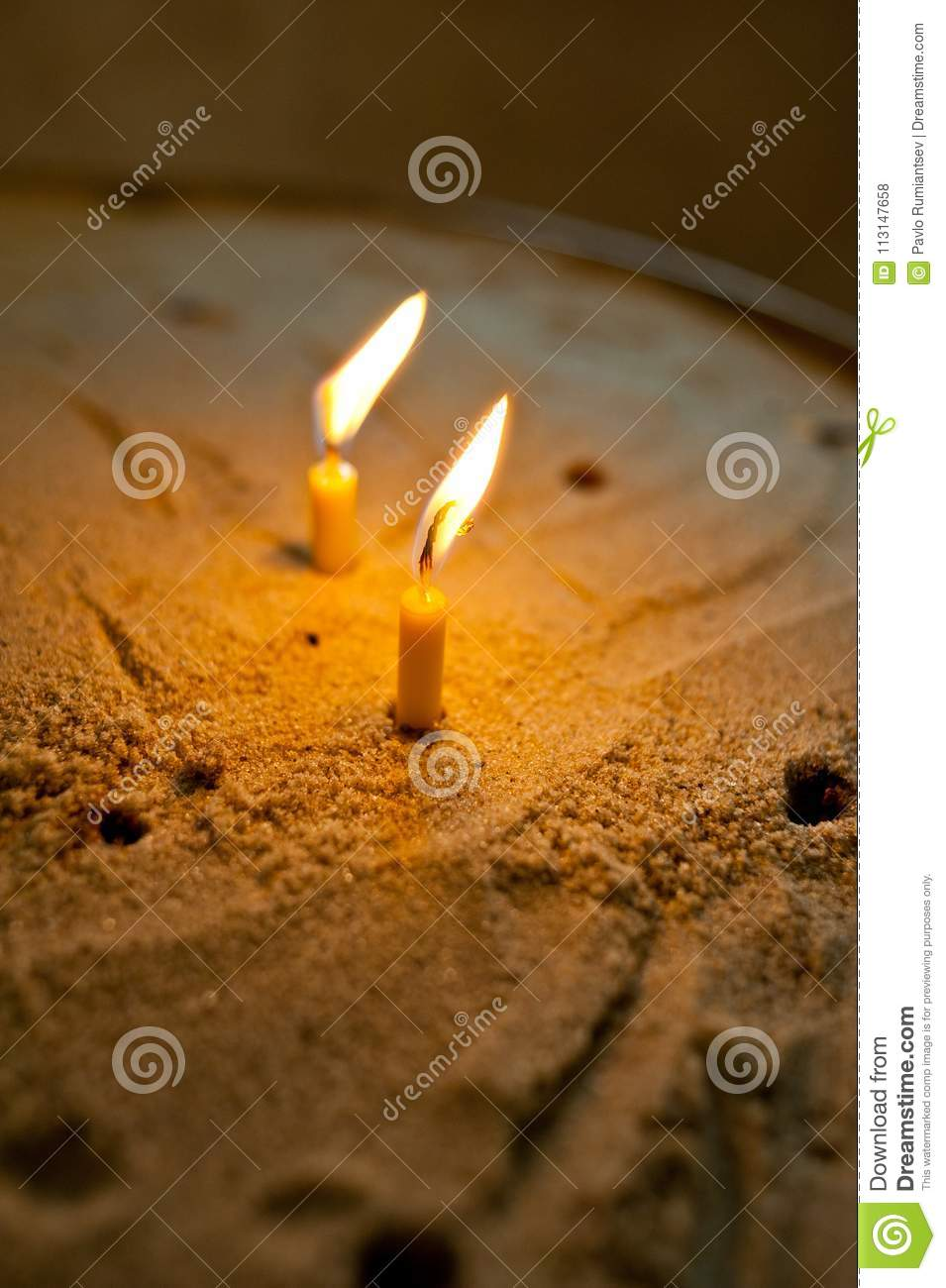 Two burning wax candles put in the sand