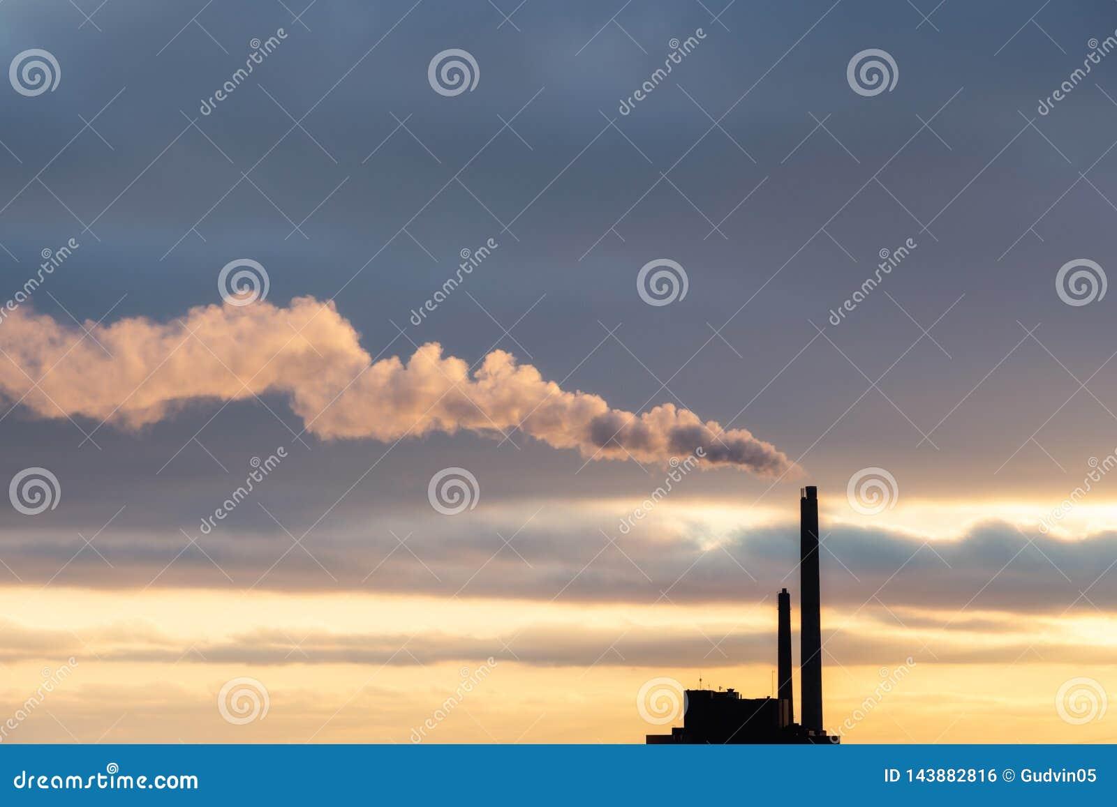 Nuage de fumée lourd de cheminée industrielle dans le coucher du soleil avec l espace de copie