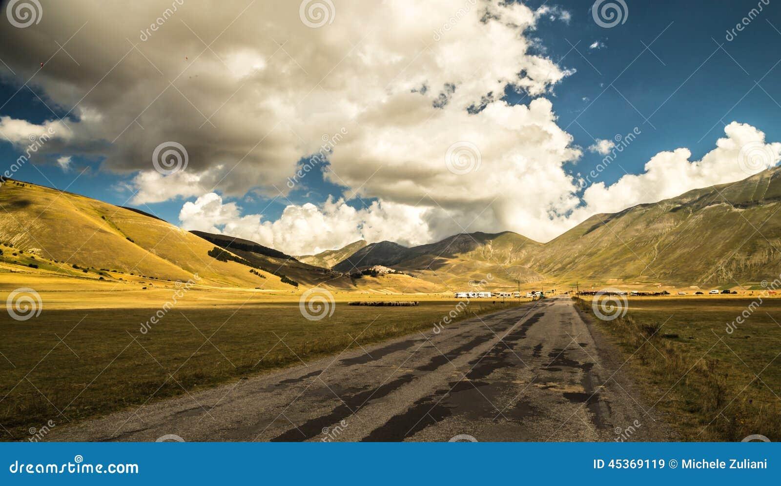 Nuages dans le ciel sur la route à Castelluccio, Italie