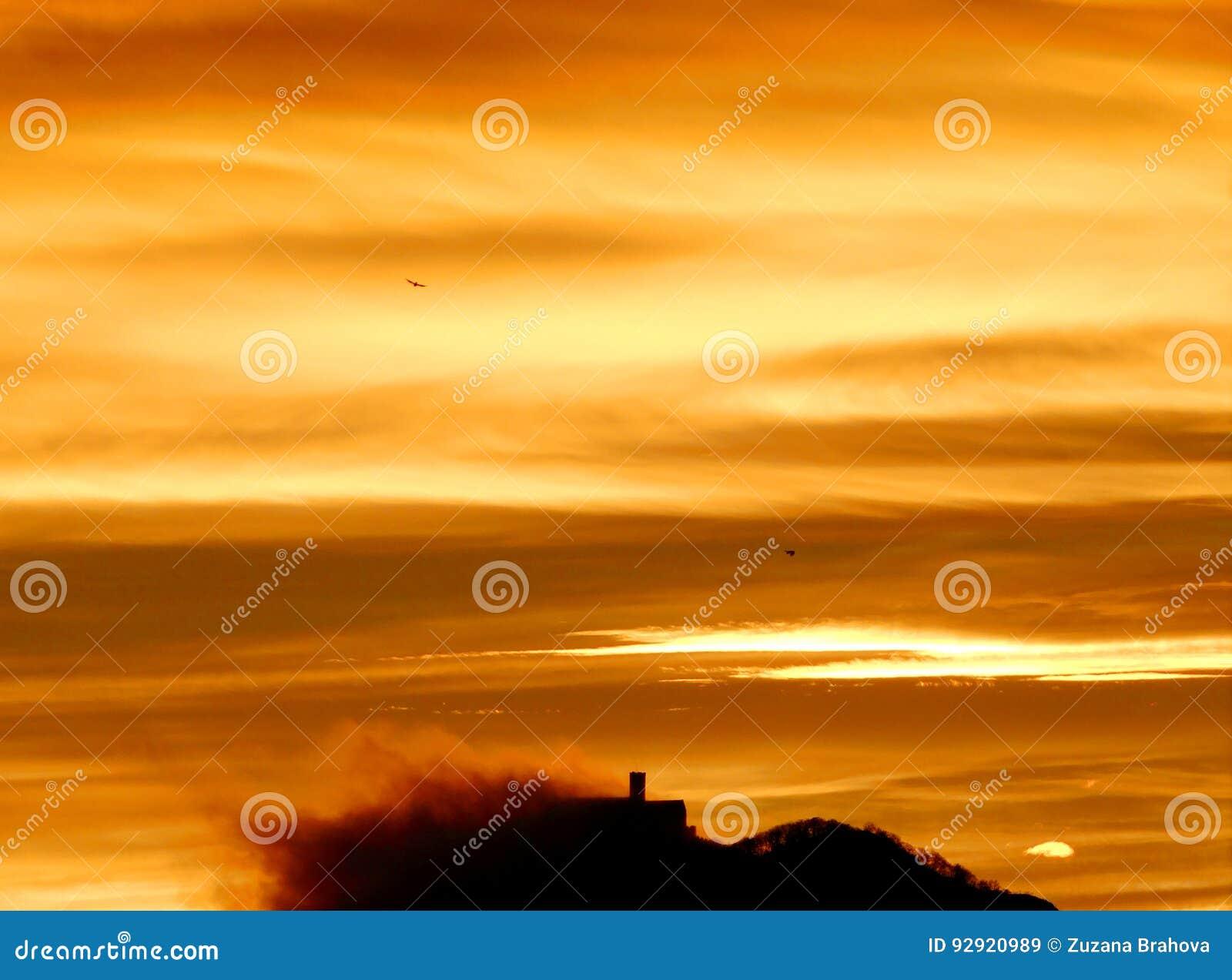 Nube behing ocultada castillo durante salida del sol