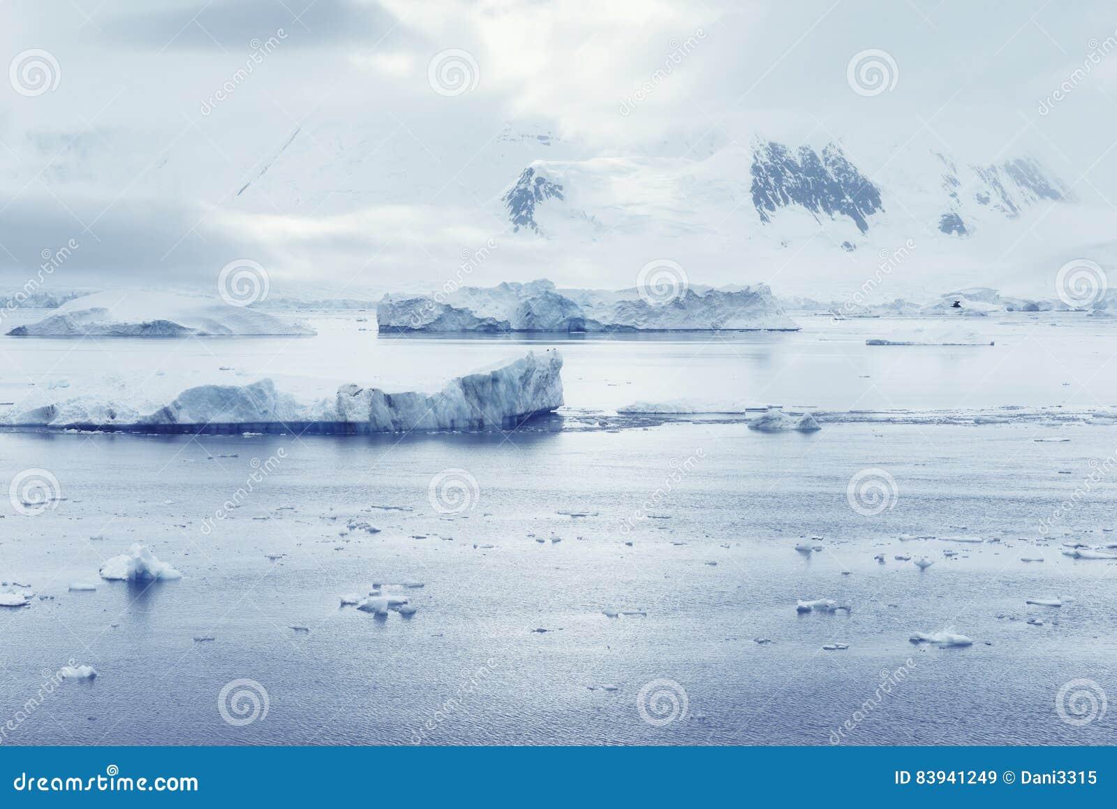 Nubes bajas sobre las montañas y los pedazos de la flotación del hielo del centro de investigación de Lockroy del puerto