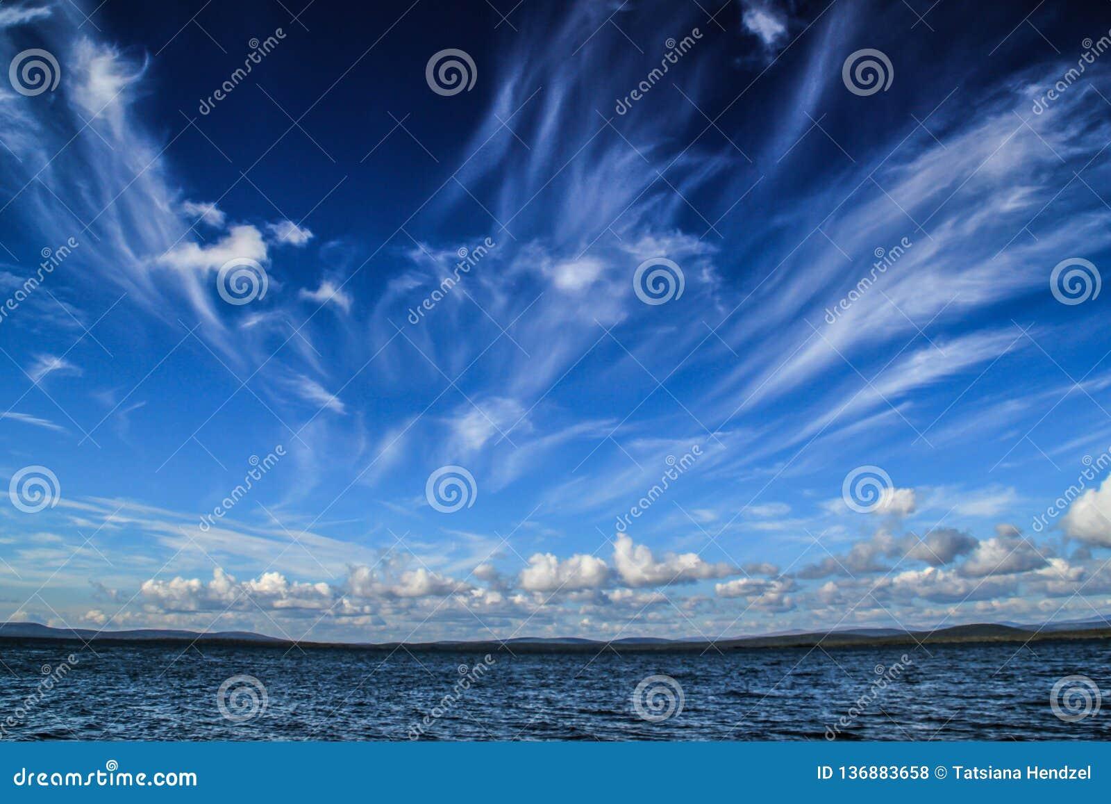 Nubes blancas vagas fantásticas contra un flotador azul marino del cielo