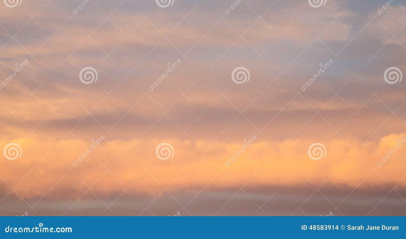 Nubes de tormenta rosadas en capas de líneas en la puesta del sol