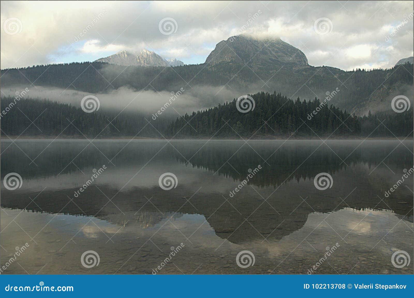 Nubla-se o lago da montanha na névoa antes do alvorecer