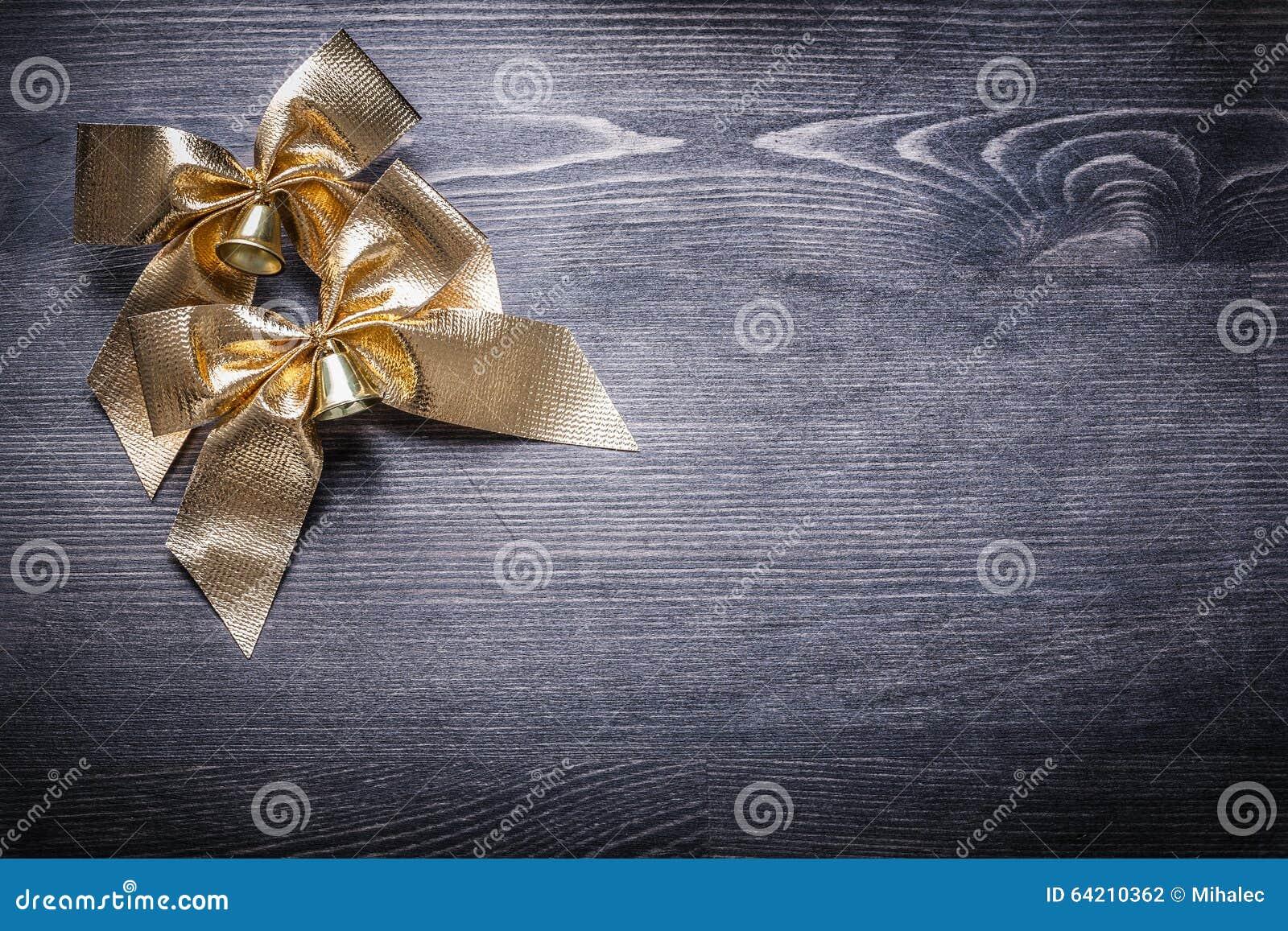 Nudos goldish de la Navidad con las campanas en el tablero de madera