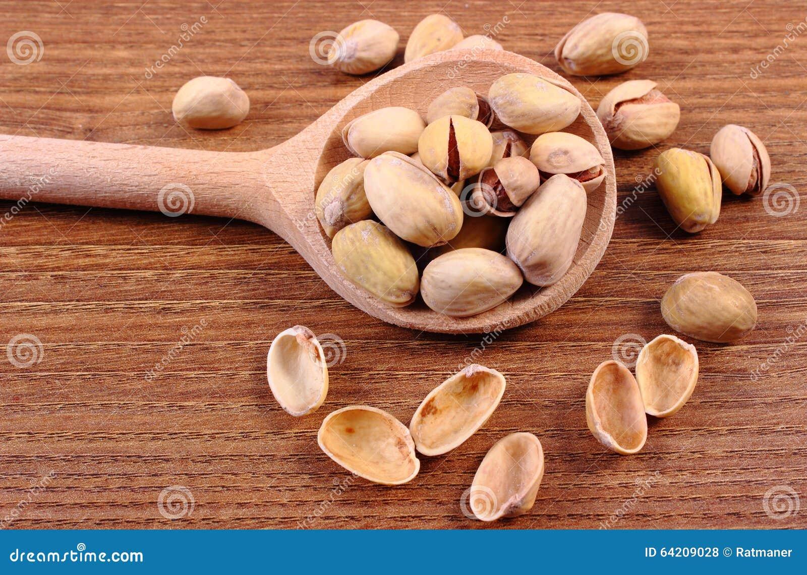 Nueces de pistacho con la cuchara en la tabla de madera, consumición sana