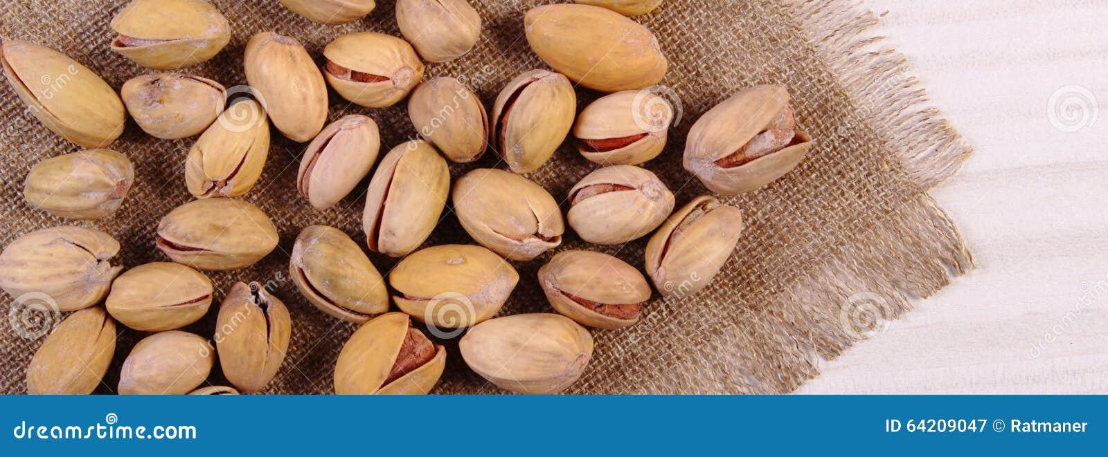 Nueces de pistacho en la tabla de madera blanca, consumición sana