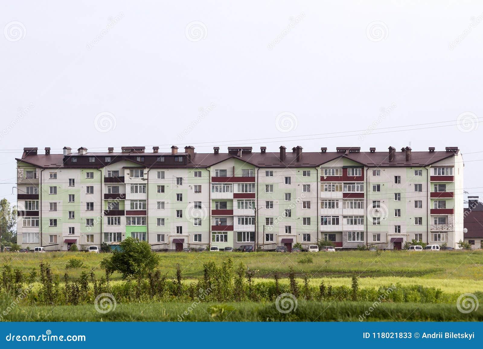 Nueva construcción de viviendas residencial moderna de la Cinco-historia en campo verde debajo del cielo claro con el tejado de l