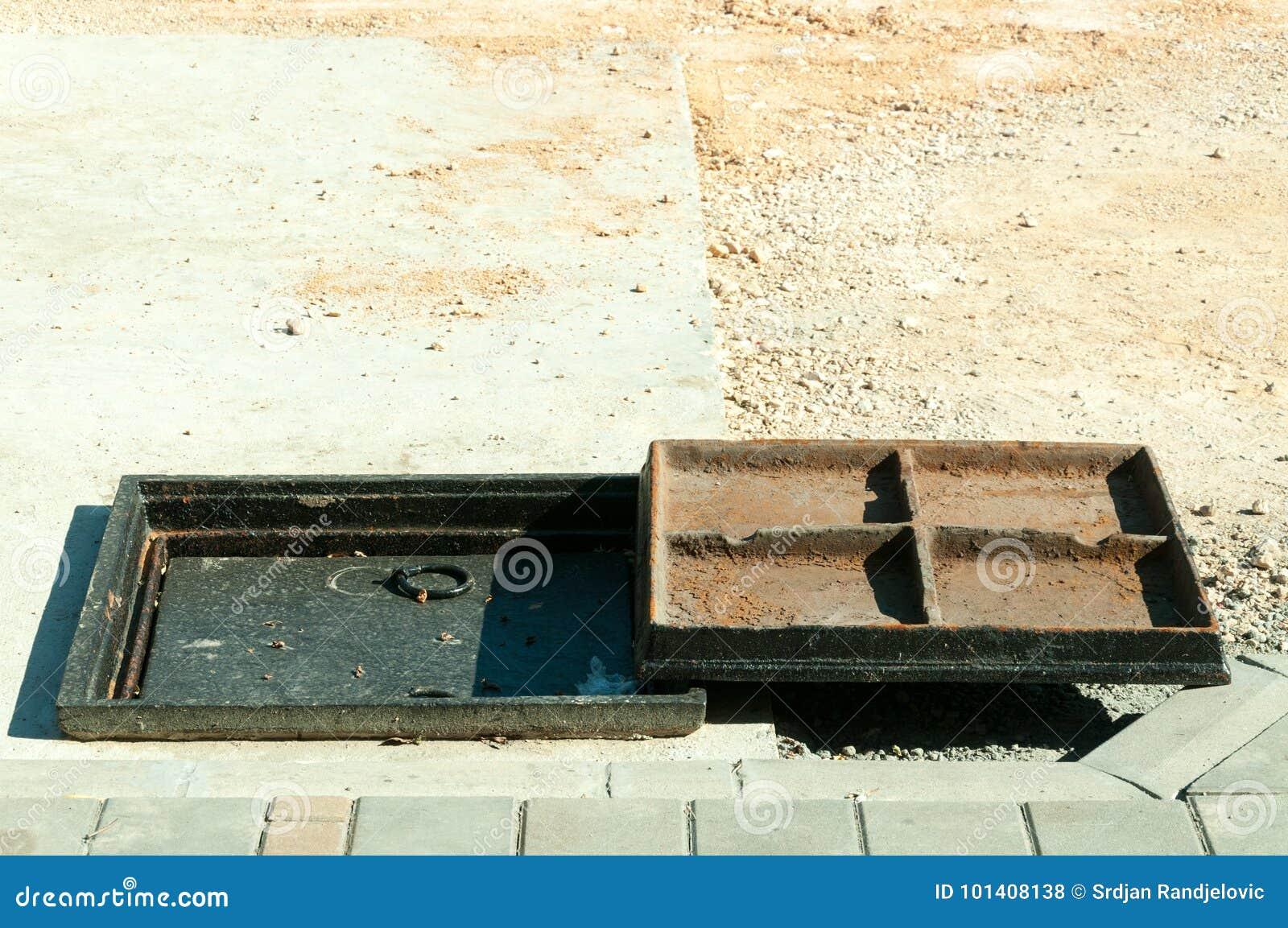 Nueva cubierta del metal sobre la boca concreta en el cierre del sitio de la construcción de carreteras para arriba