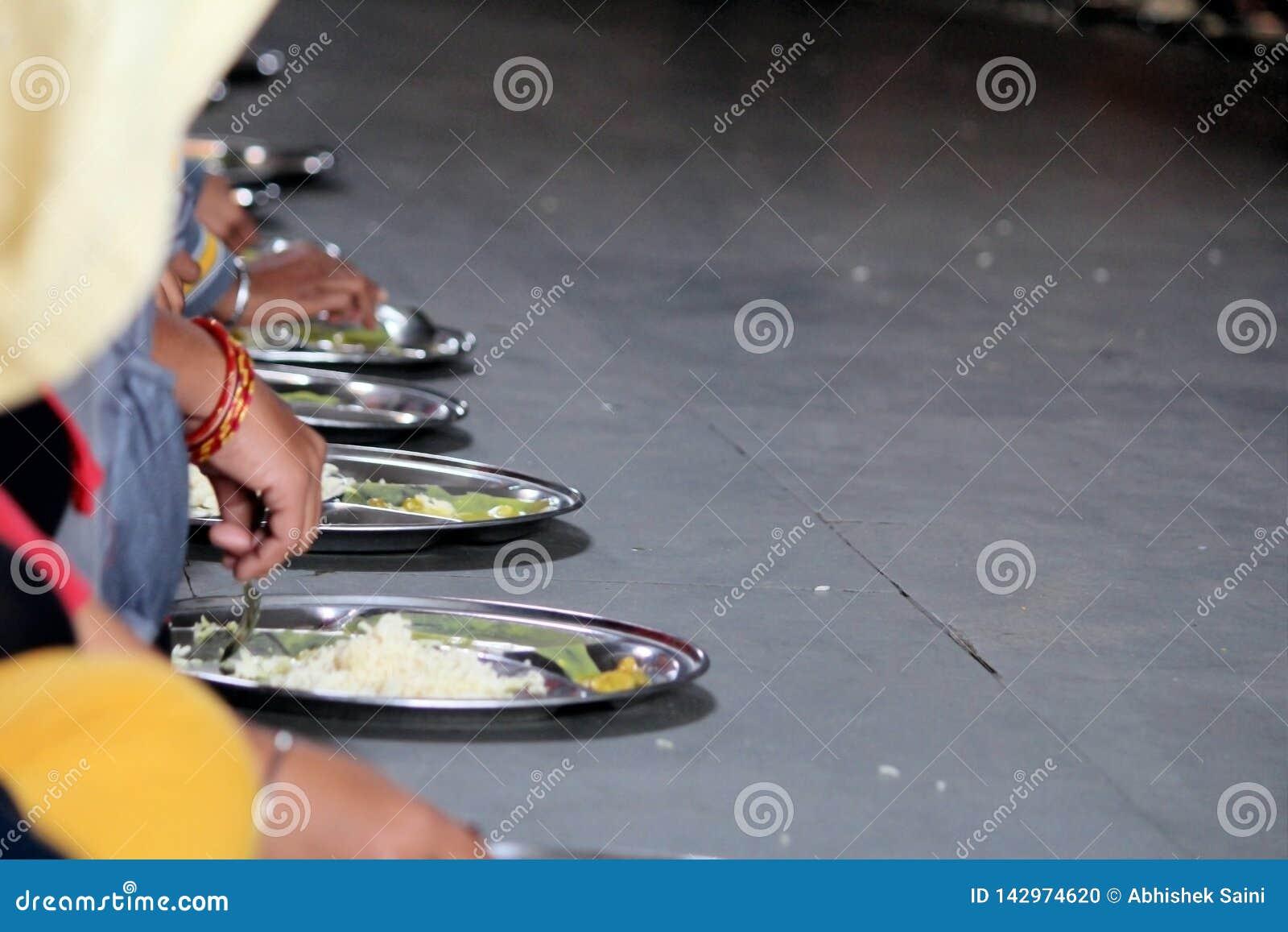 NUEVA DELI, la INDIA - 21 de marzo de 2019: los peregrinos comen comidas libres en el templo de oro Gurudwara Bangla Sahib en Del