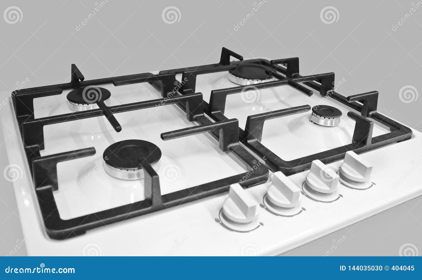 Nueva estufa de gas moderna con cuatro hornillas para la cocina, superficie esmaltada blanca