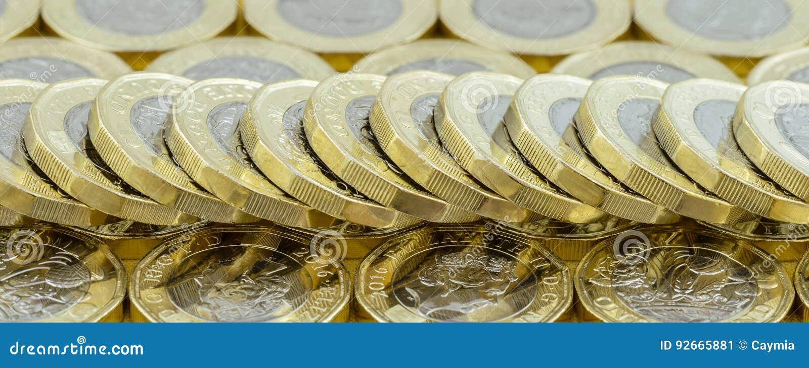 Nueva pila caída separada de las monedas de libra del dinero británico