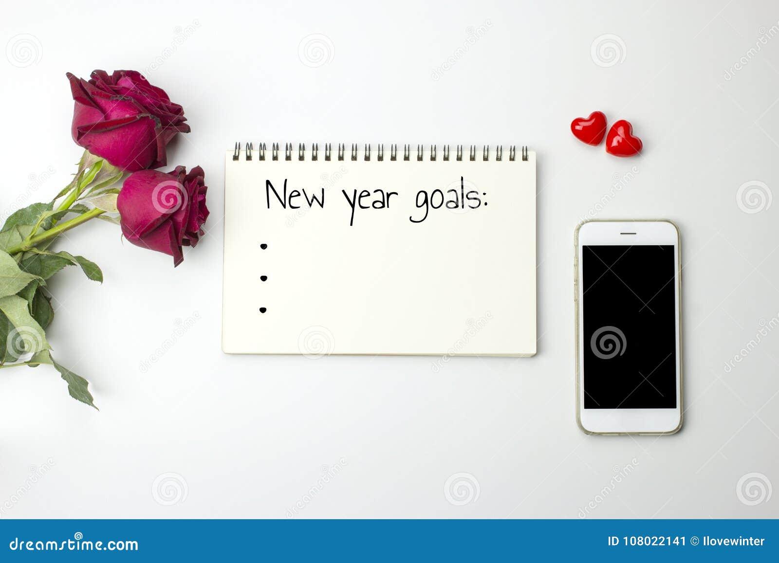 Nuevas palabras de las metas del year' s en el cuaderno con las rosas y el teléfono elegante