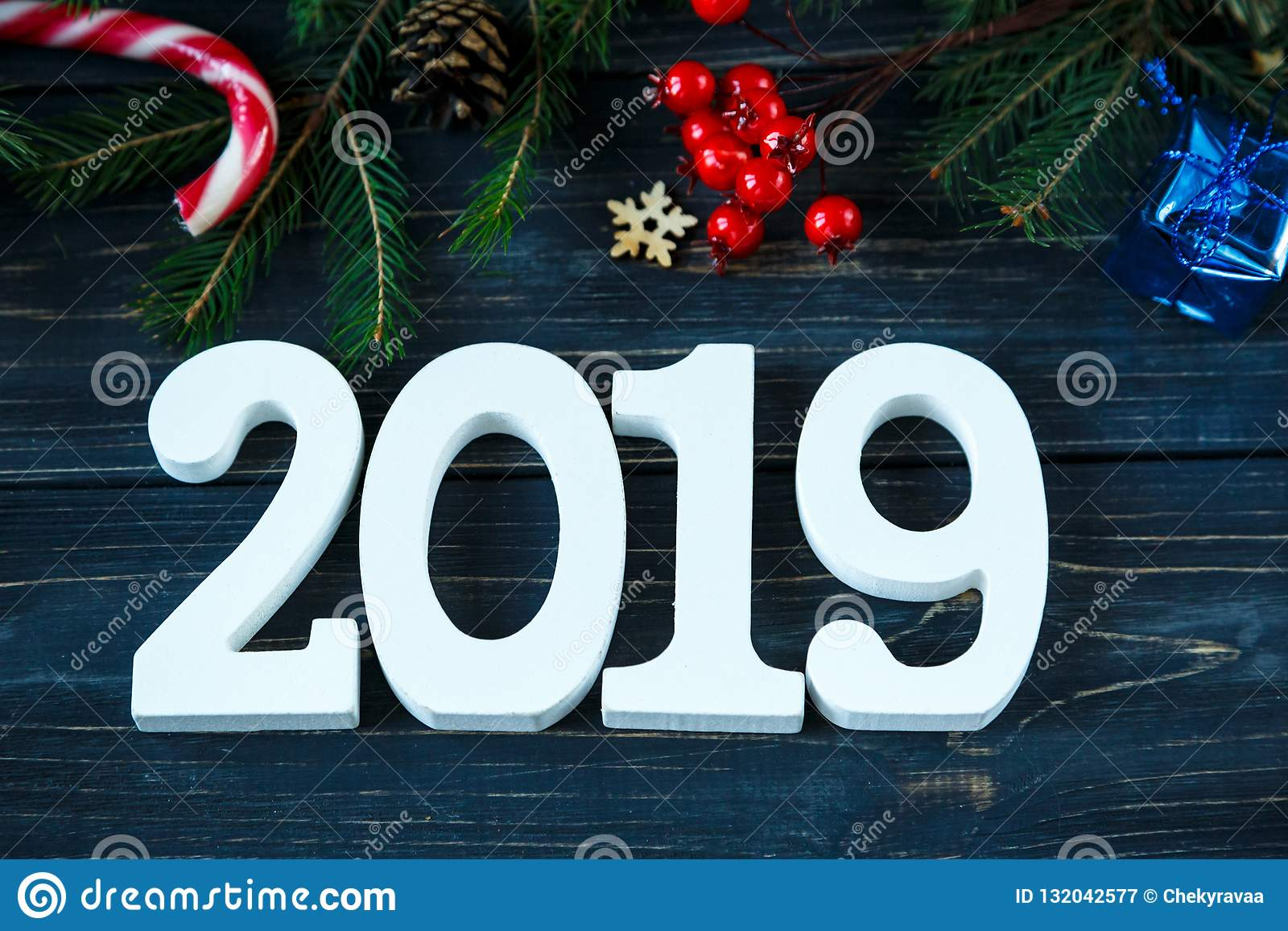 2019, branches of fir tree, decor on grey wooden table. New Year Goals list, things to do on Christmas
