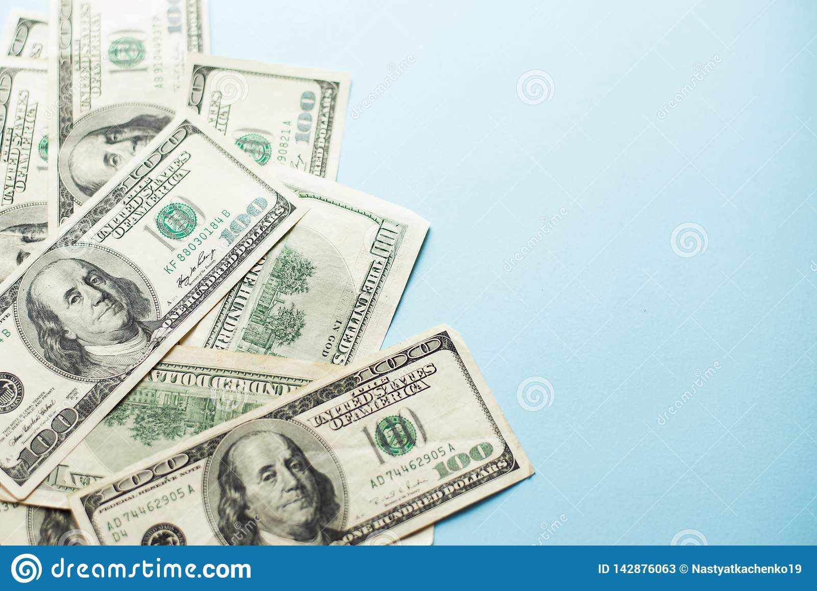 A number of one hundred US dollar notes on light blue background. concept