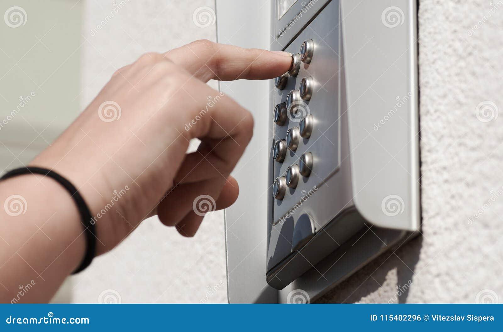 Numerisches Kodierungsgerät der Tür auf dem Gebäude, mit der weiblichen Hand