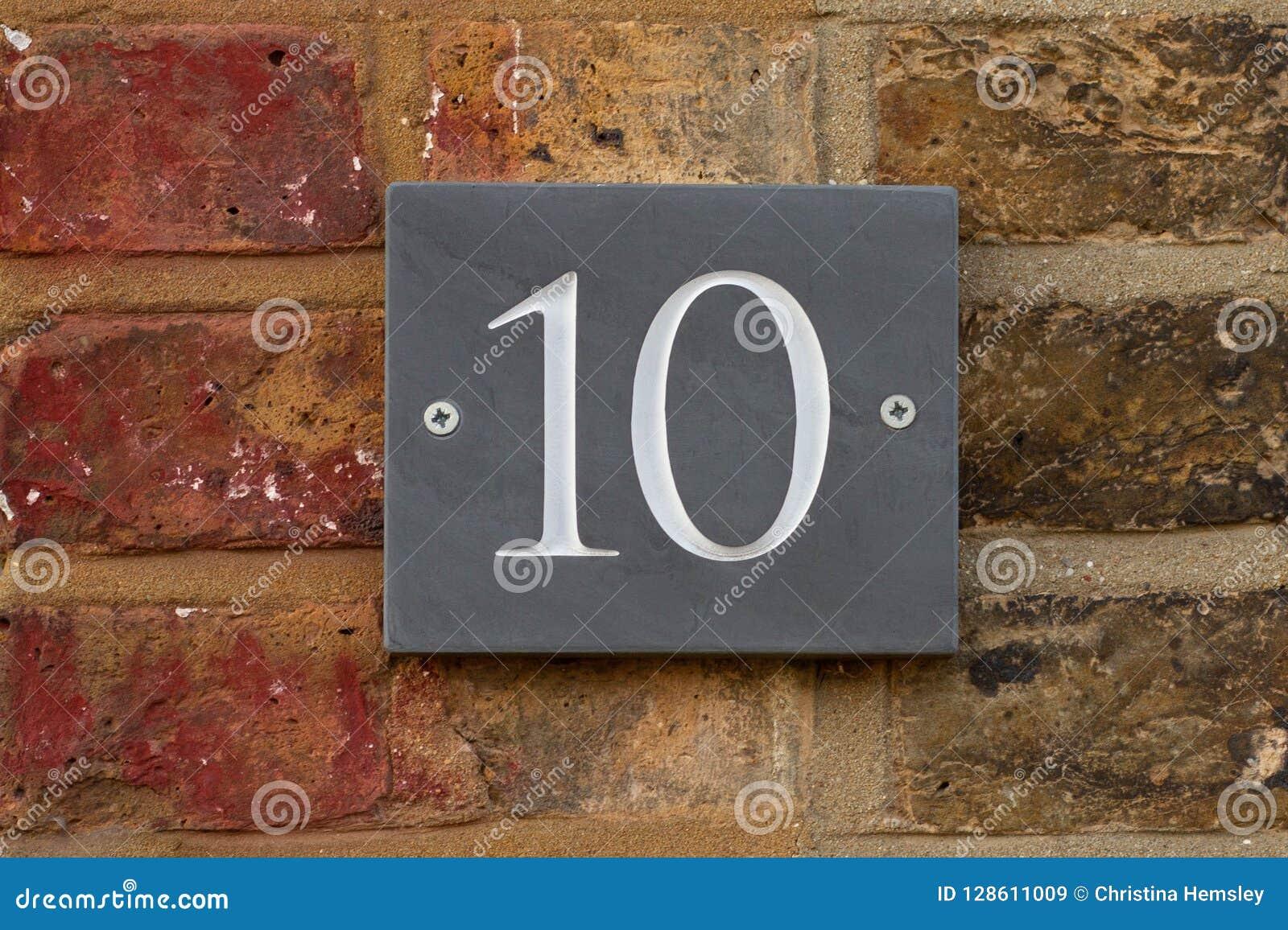 Numero civico 10 su un muro di mattoni su unardesia grigia immagine