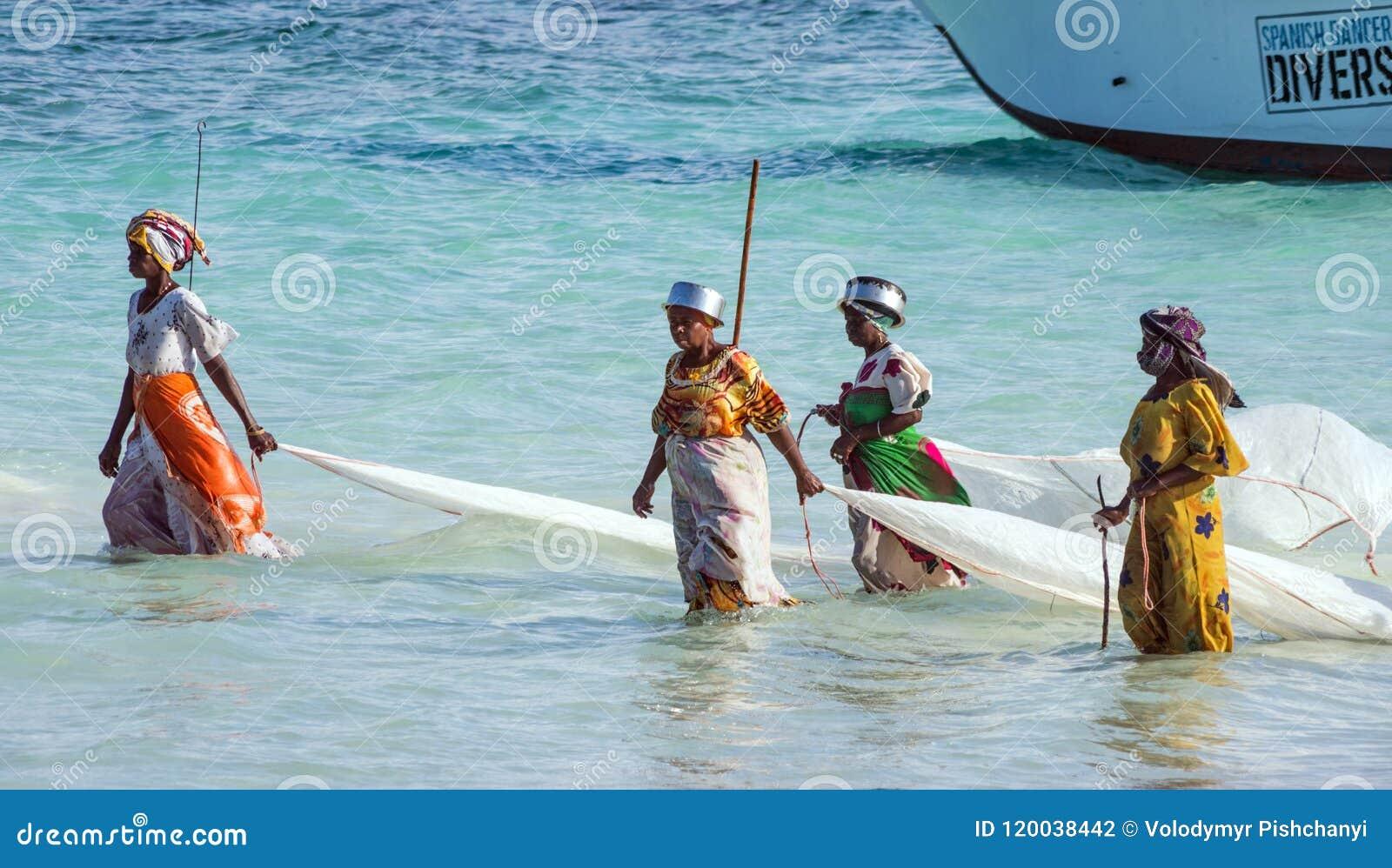 Nungwi, Zanzibar, Tanzania, Africa orientale - 23 giugno 2017: Donne africane da un paesino di pescatori per prendere le piccole