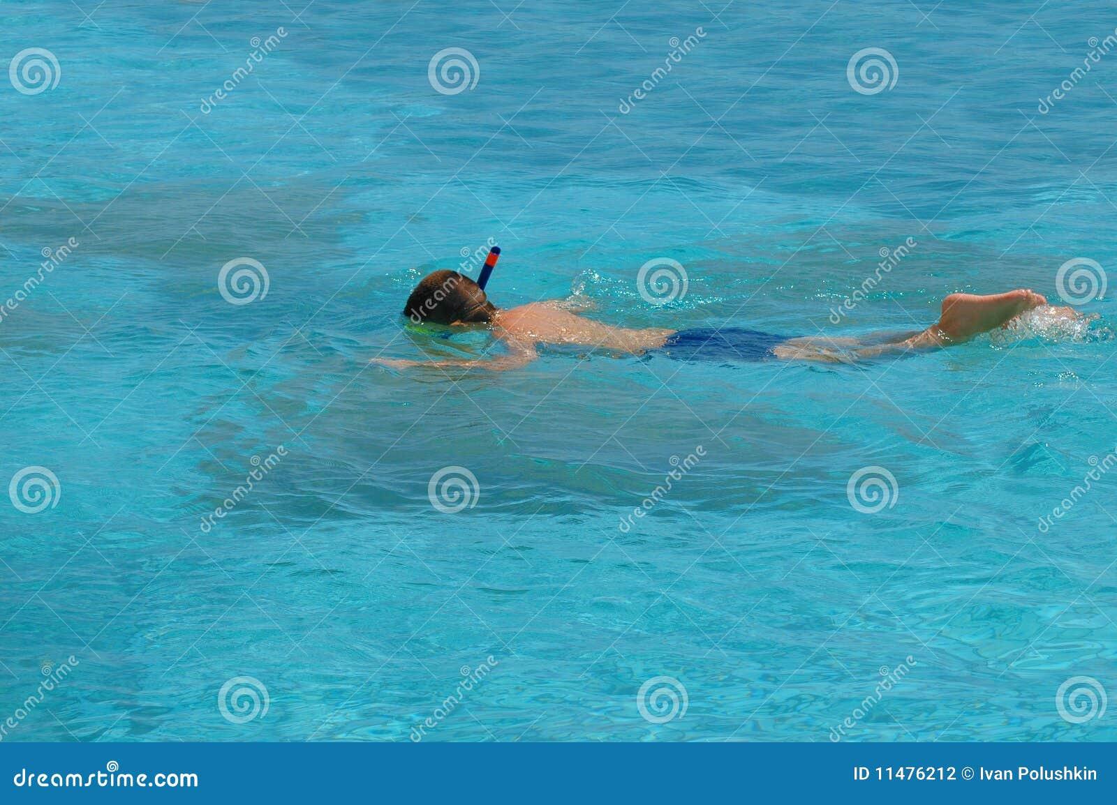 Nuoto del ragazzo con la mascherina