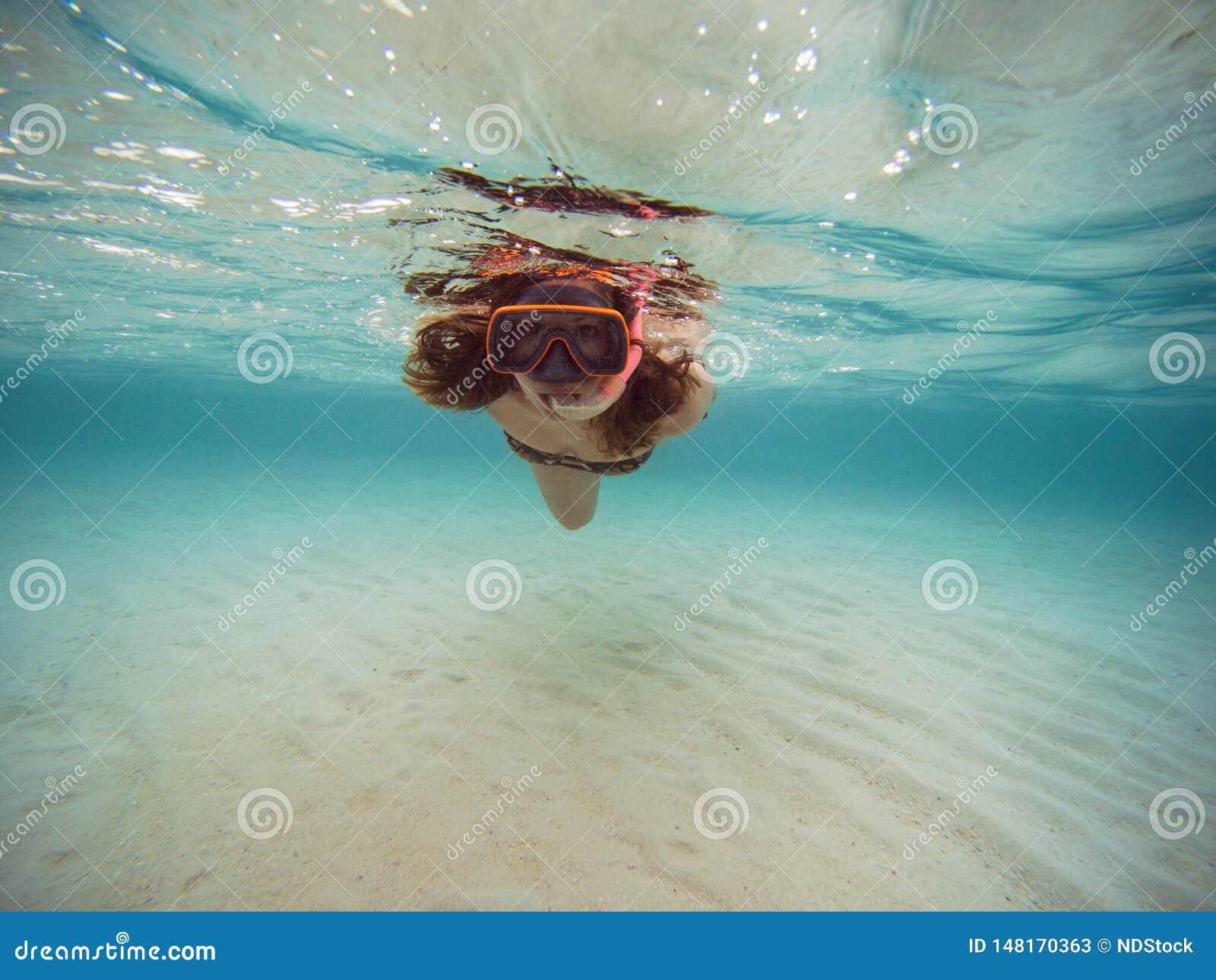 Nuoto della giovane donna e immergersi con la maschera e le alette in chiara acqua blu