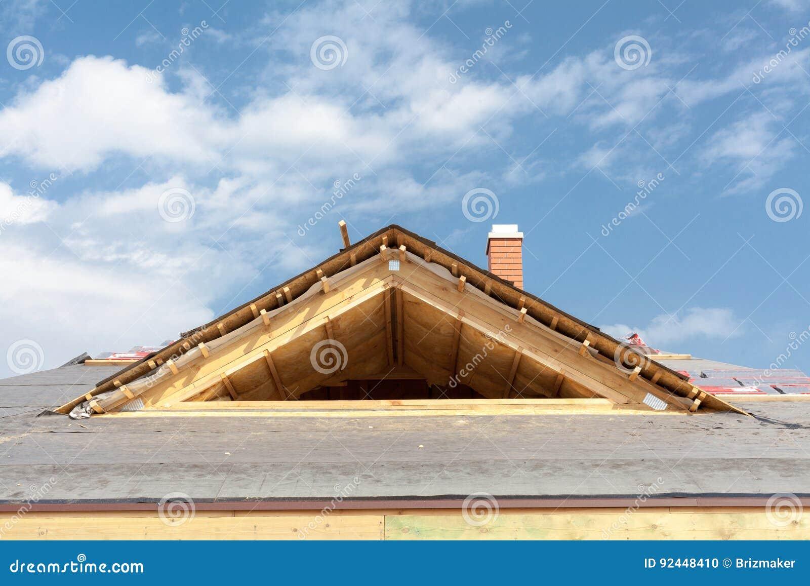 Nuova casa di legno in costruzione Tetto con le assicelle dell asfalto, il camino ed il materiale di isolamento