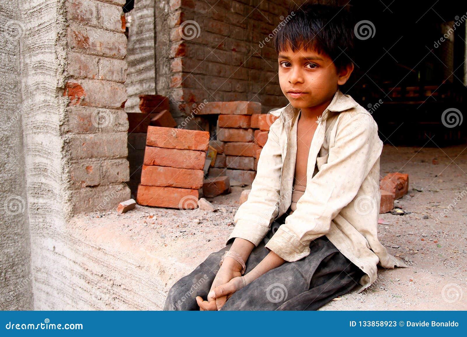 Nuova Delhi, India - 20 ottobre 2017: ritratto di giovane ragazzo indiano che lavora come muratore nella costruzione con i vestit