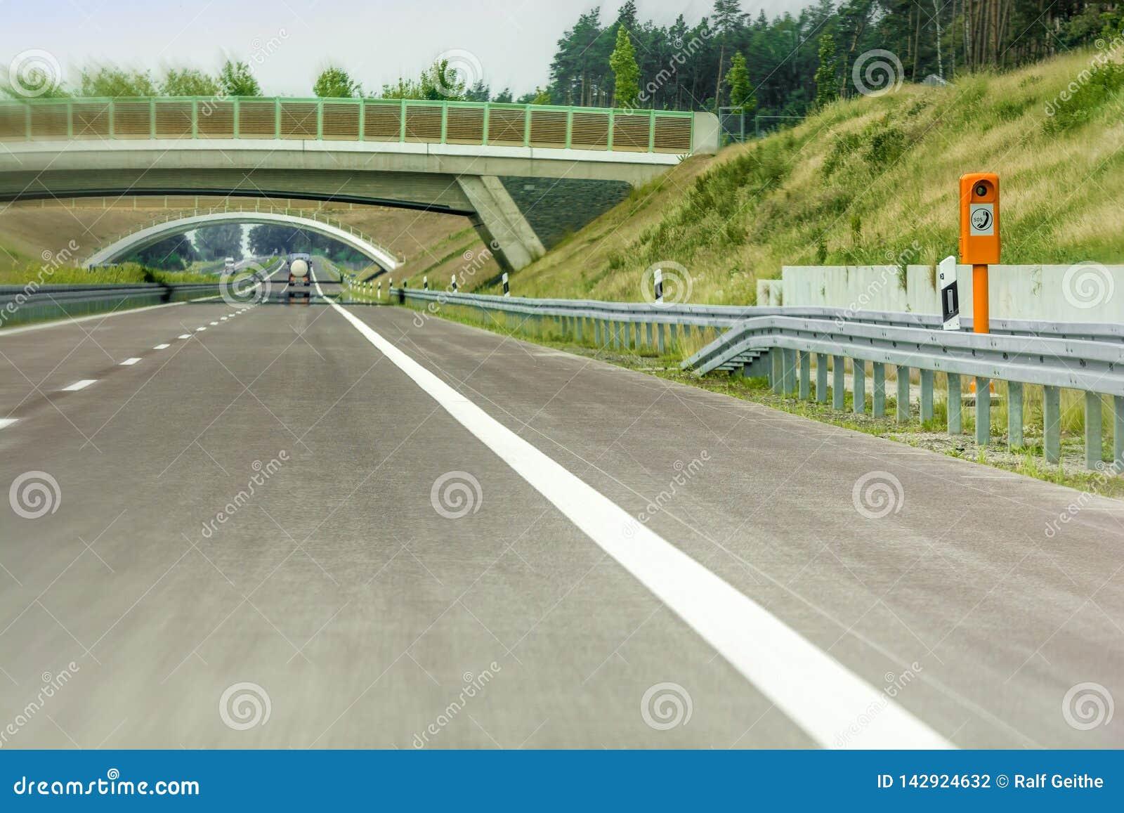 Nuova sezione dell autostrada con la chiamata d emergenza ed il ponte verde