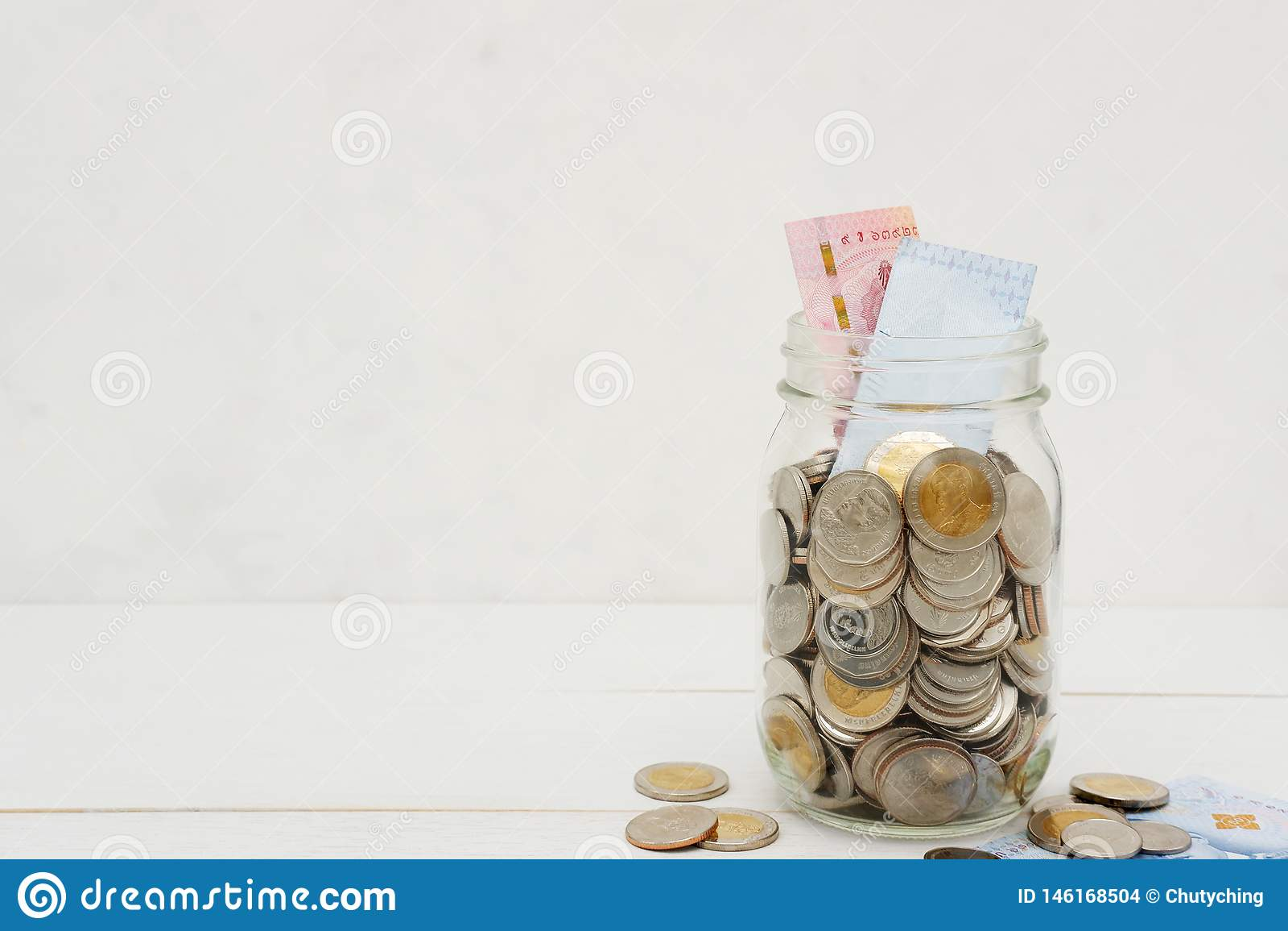 Nuove banconote e monete di baht tailandese in un barattolo di vetro, sulla tavola di legno bianca