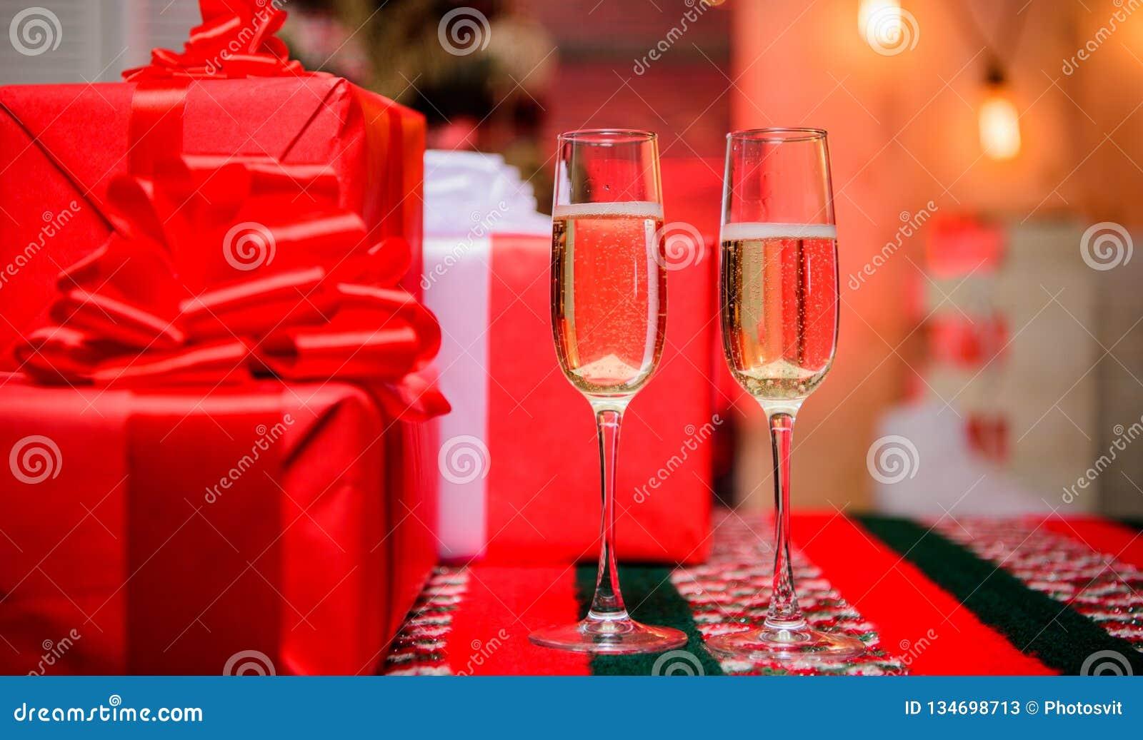 Nuovo anno felice e Buon Natale Il vetro ha riempito il vino spumante o il champagne vicino ai contenitori di regalo Incoraggia i