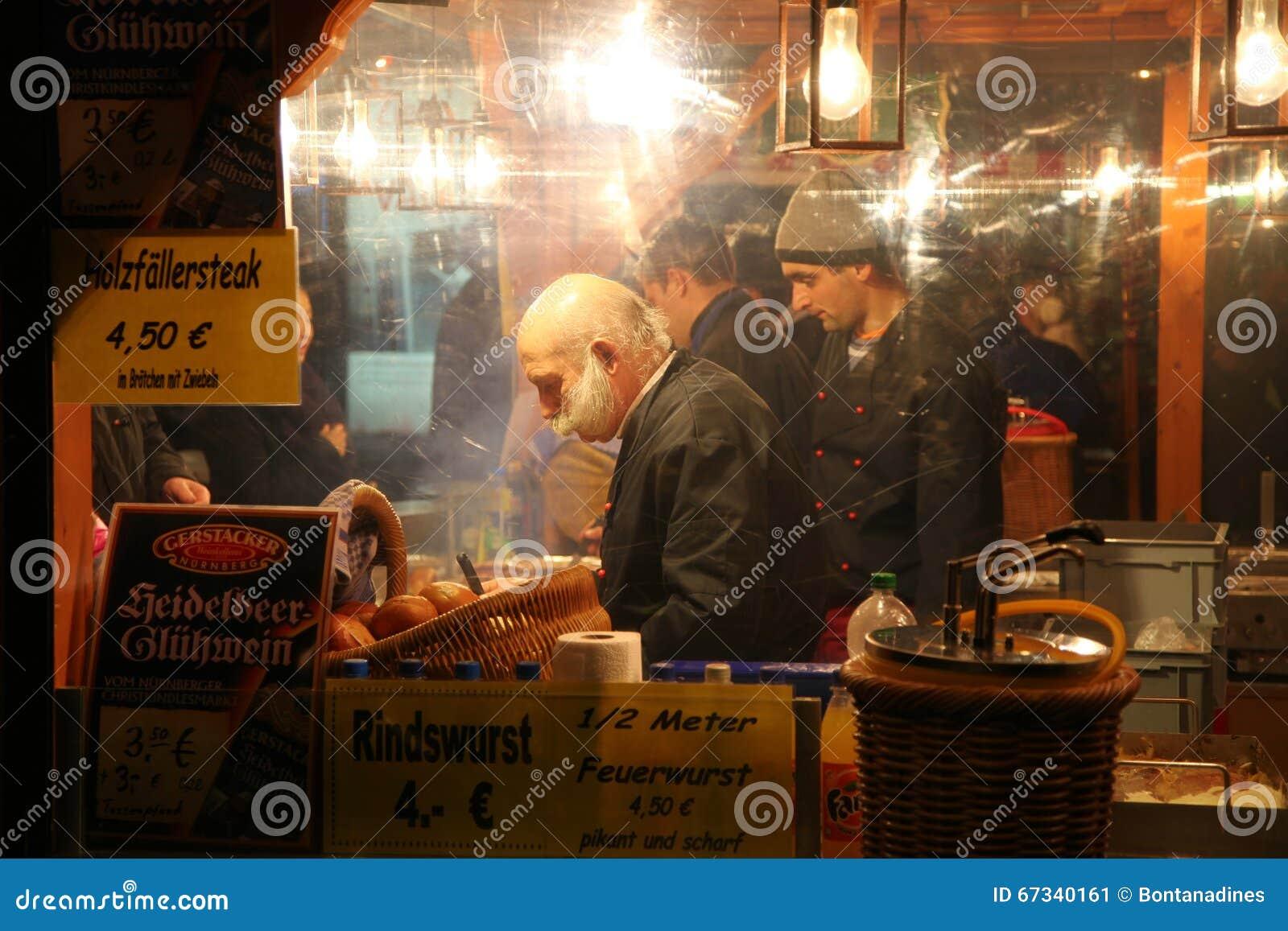 NUREMBERG TYSKLAND - DECEMBER 22, 2013: Den stilfulla representanten säljer korvar på natten på julmässan, Nuremberg, Tyskland