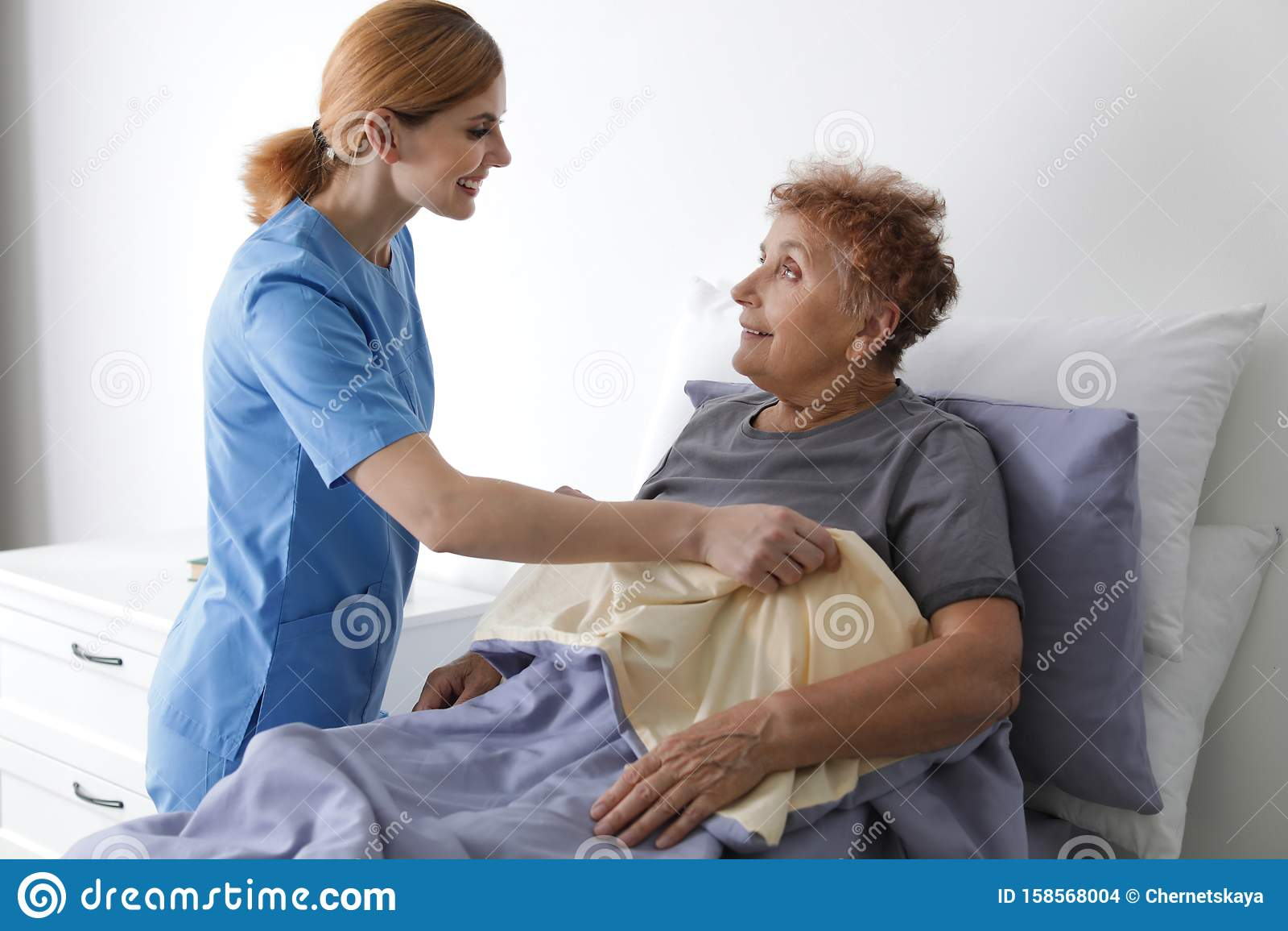 Nurse assisting elderly woman in bed
