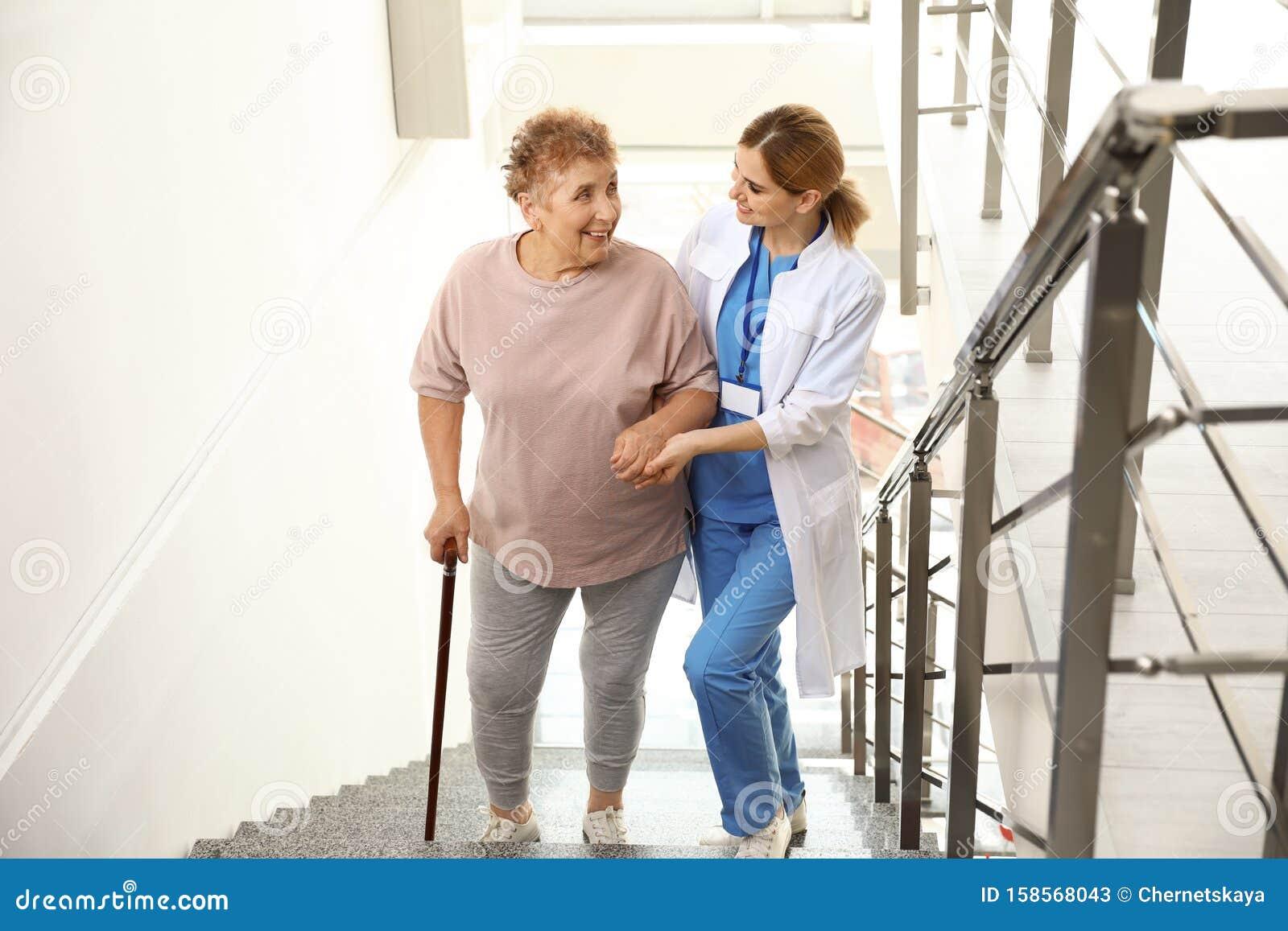 Nurse assisting elderly woman on stairs