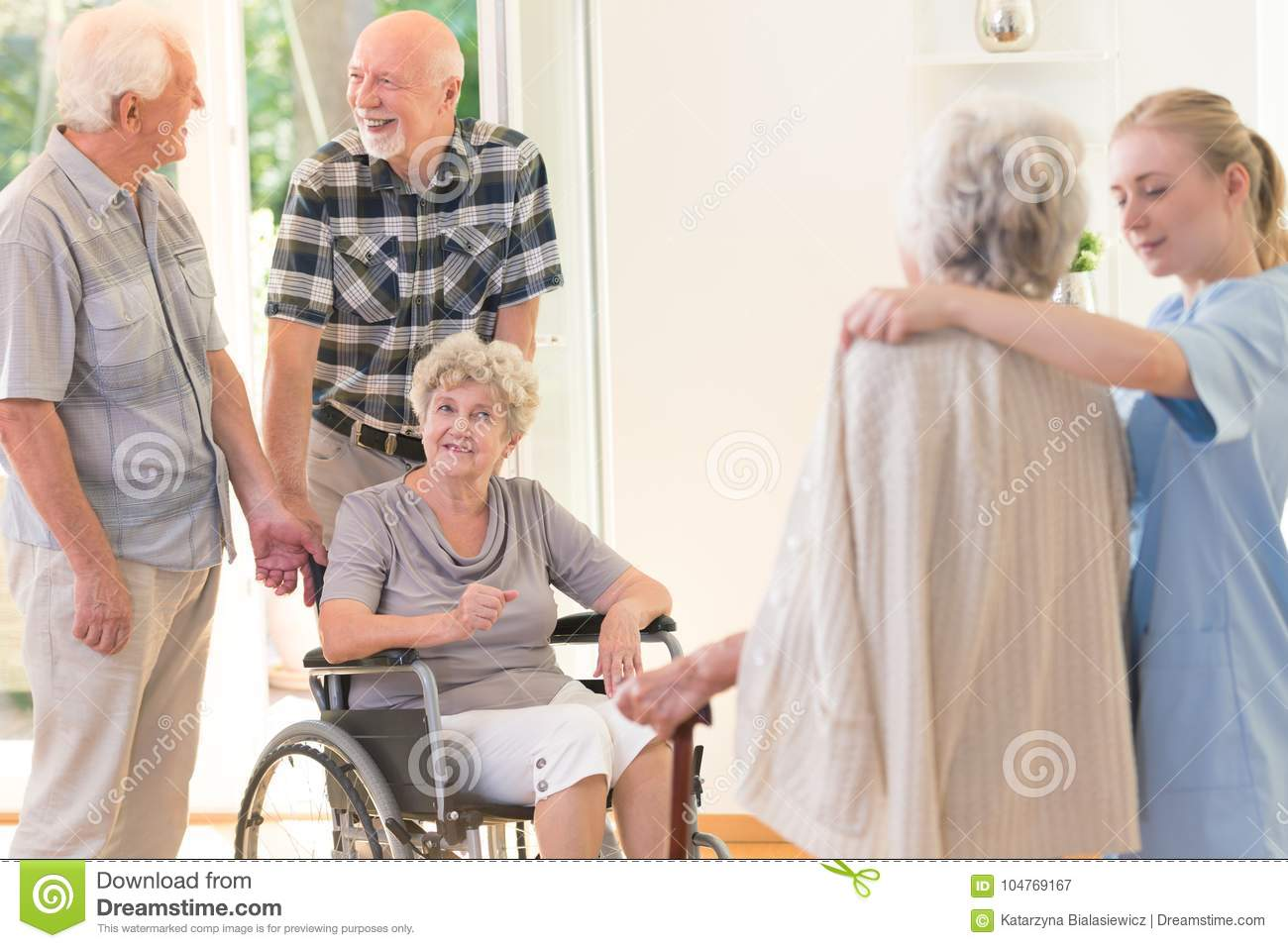 Elderly man supporting disabled wife