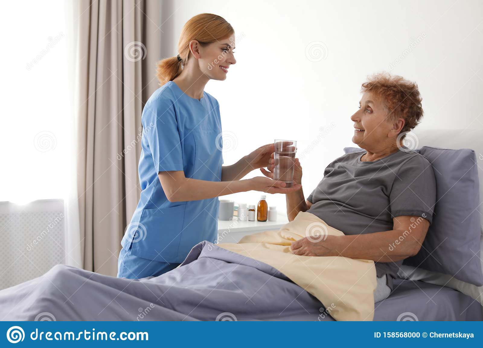 Nurse giving glass of water to elderly woman. Medical assistance