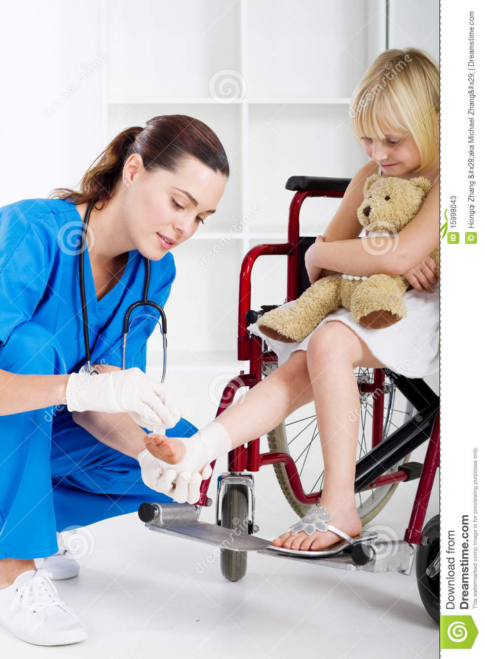 kind young caring nurse helping a little girl patient in wheelchair ...